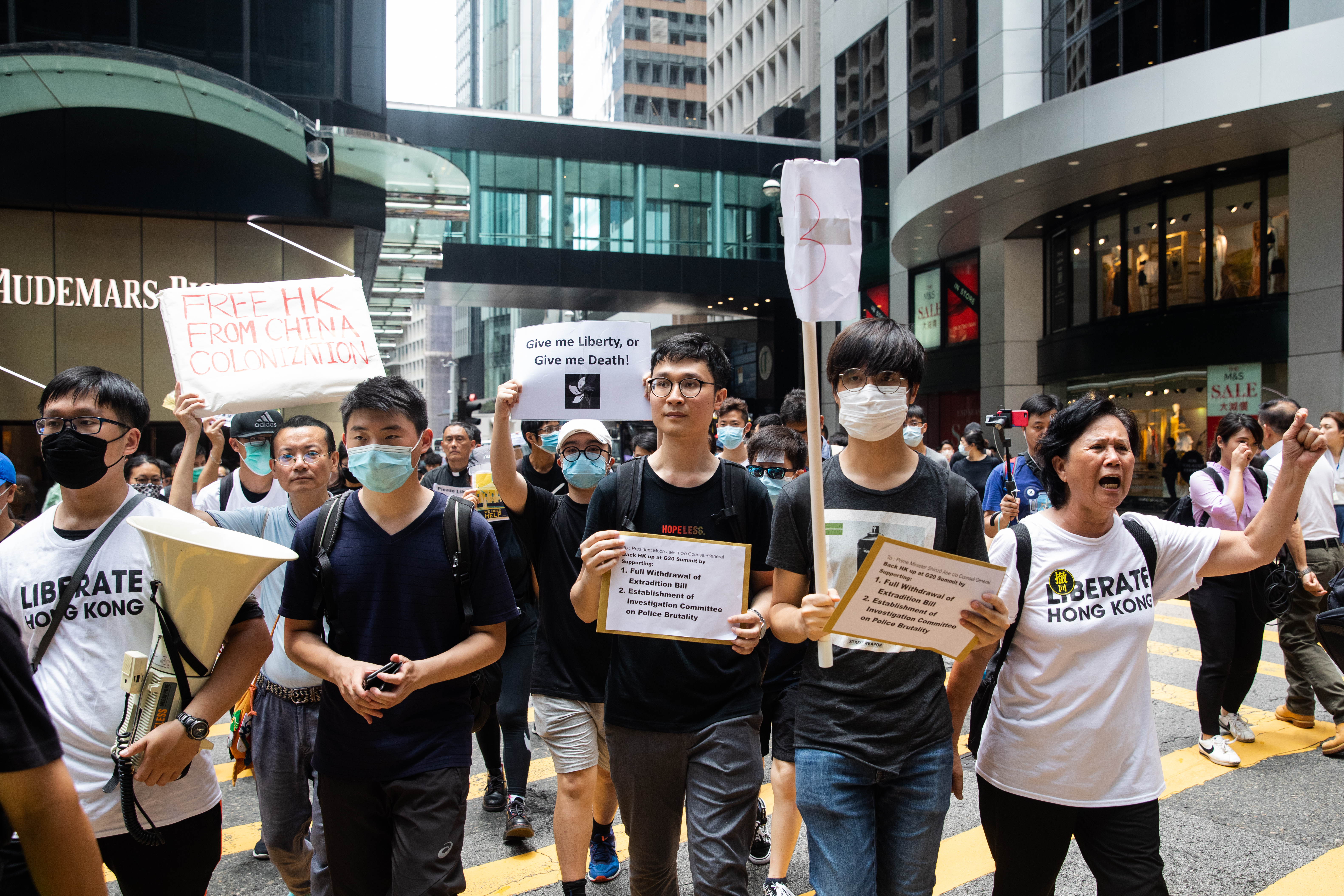 Ventus Lau (C) leads a march to deliver letters to local G-20 consulates urging global intervention against a proposed extradition bill in Hong Kong, China, on Wednesday, June 26, 2019.