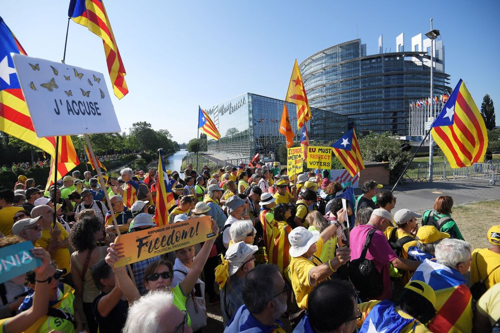 People wave Catalan pro-independence 'Estelada' flags and banners during a demonstration in front of the European Parliament on July 2 , 2019 in Strasbourg, eastern France.