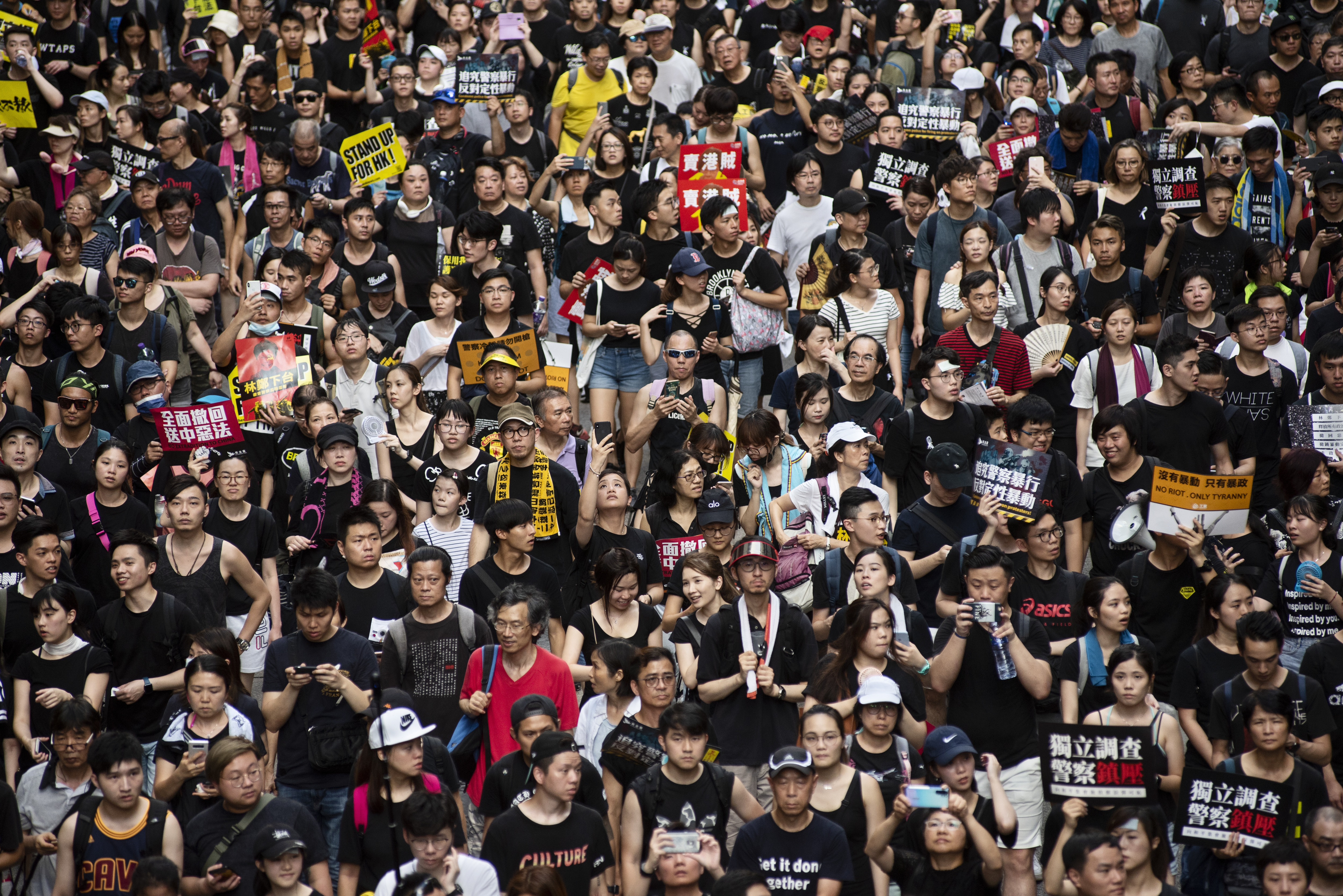 Demonstrators in Hong Kong hold anti-government placards and chant slogans during a march on July 1, 2019.
