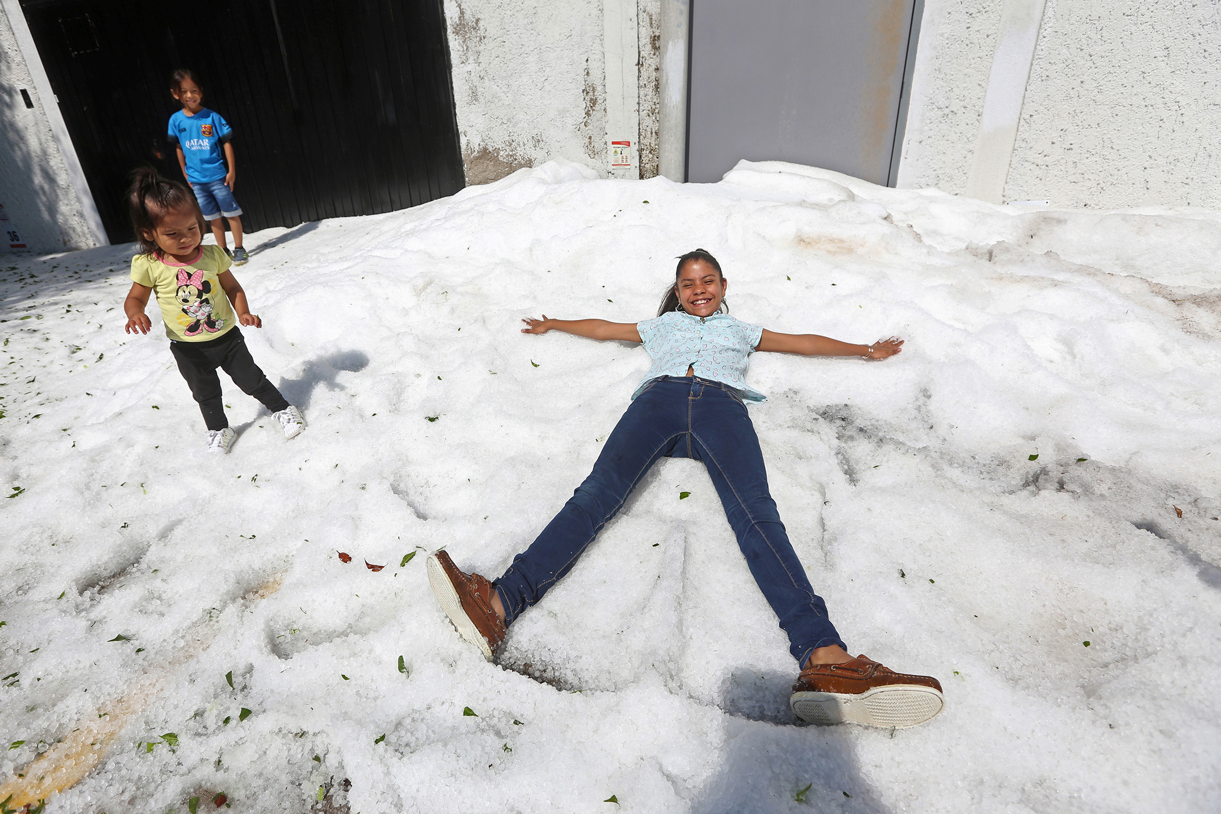 Residents play on top of ice after a heavy storm of rain and hail which affected some areas of the city in Guadalajara, Mexico on June 30, 2019.