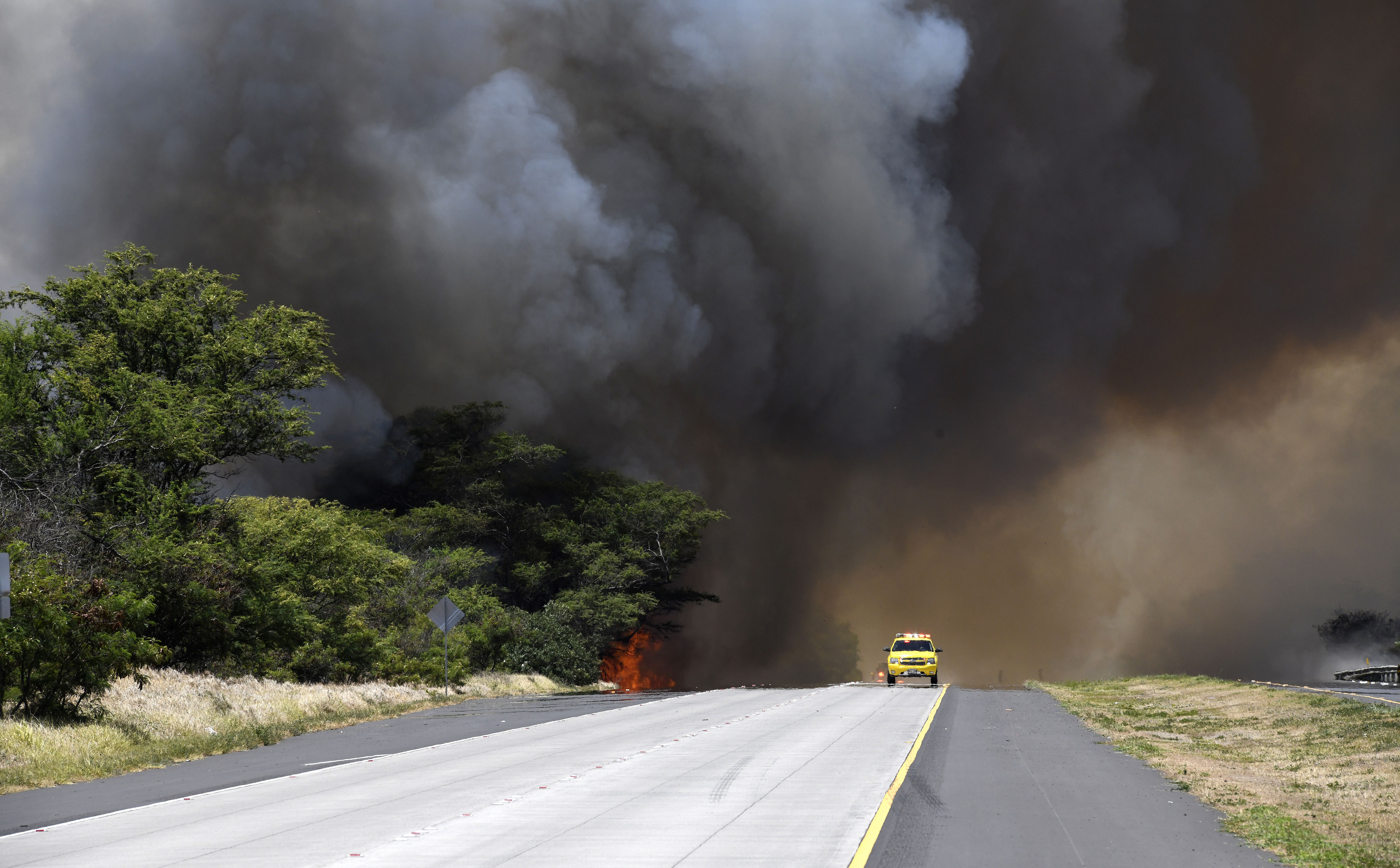 A plume of smoke from a brush fire closes Kuihelani Highway in Central Maui, Hawaii, Thursday, July 11, 2019.