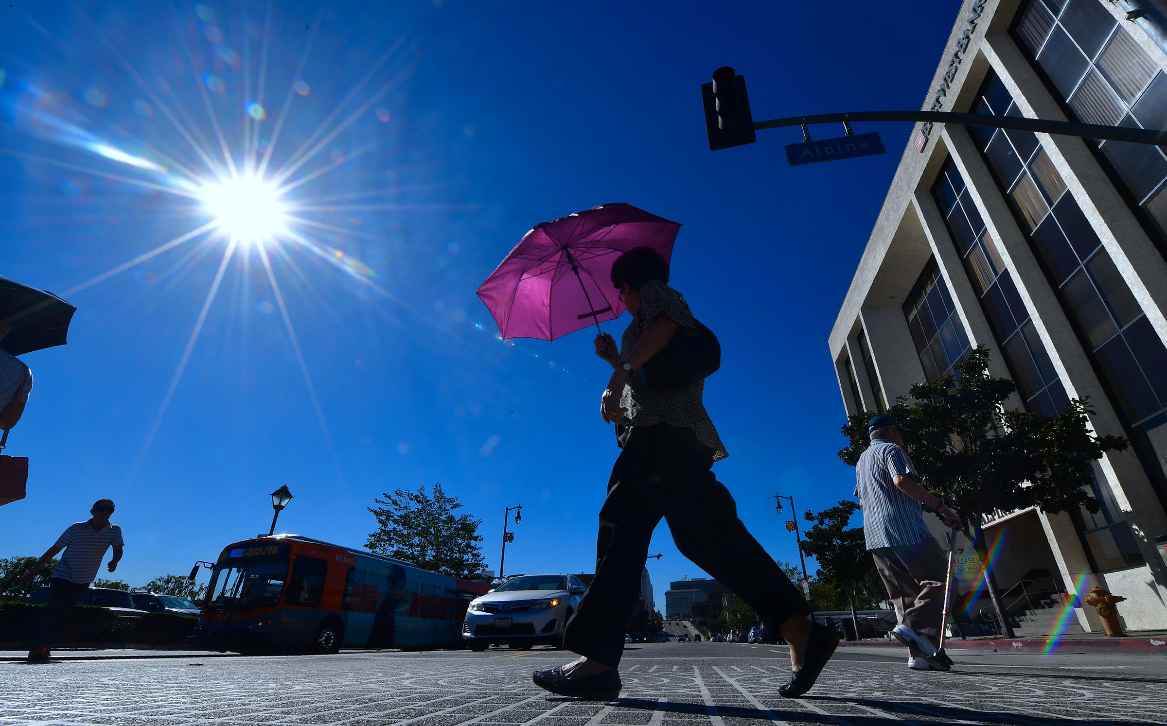 A pedestrian uses an umbrella on a hot sunny morning in Los Angeles on October 24, 2017 amid a late season heatwave hitting southern California.