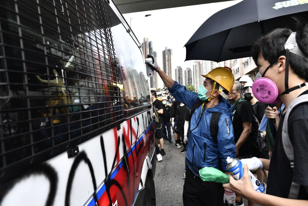 A protester puts graffiti on a police van during demonstration in the district of Yuen Long in Hong Kong on July 27, 2019.