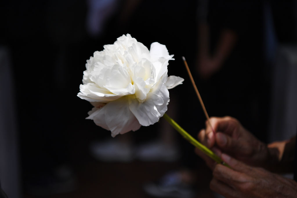A mourner holds a flower and a incense stick to be placed at the site where a protester died in Hong Kong.