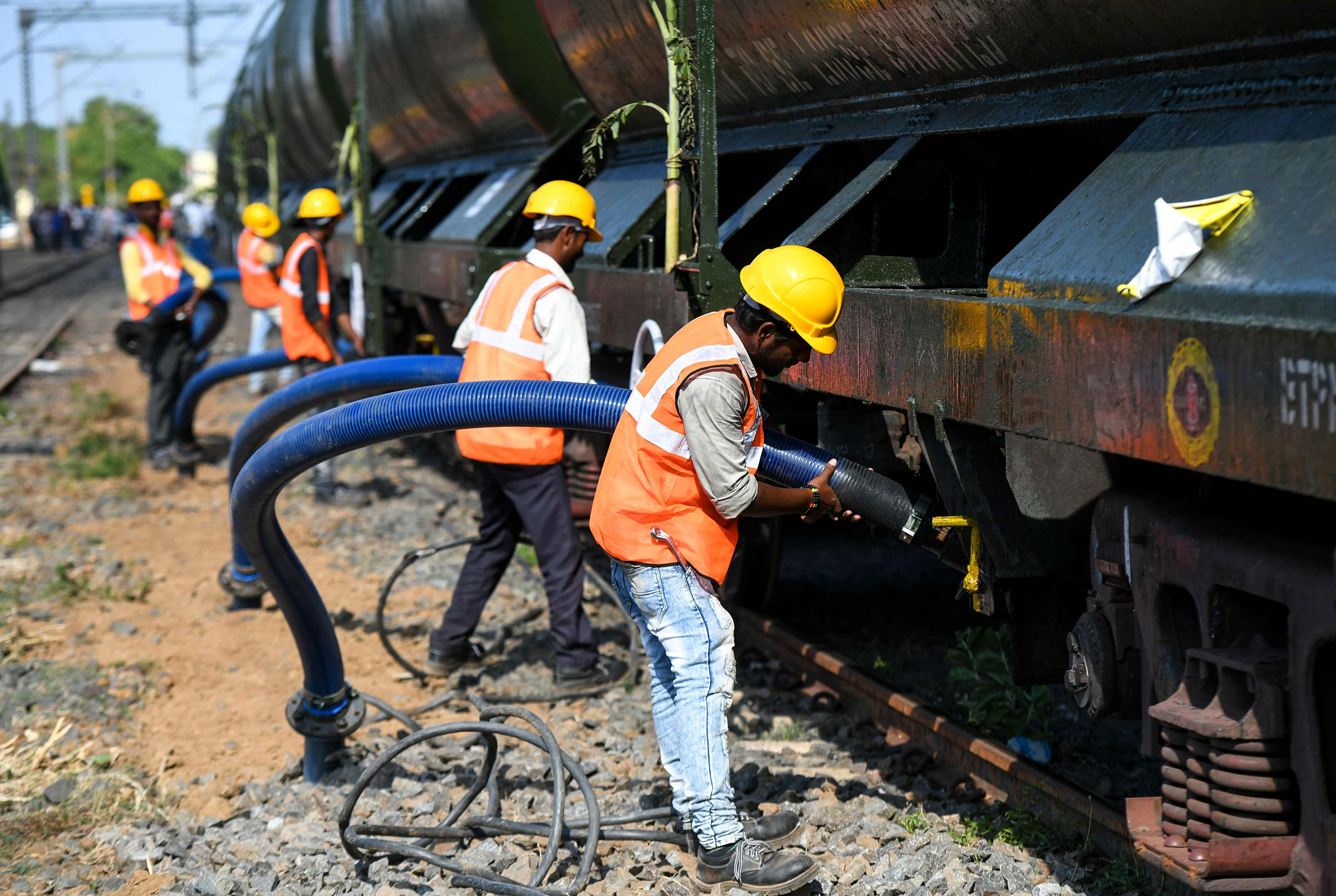 Indian laborers connect pipes to collect water from a train carrying liters of water at a railway station in Chennai on July 12.