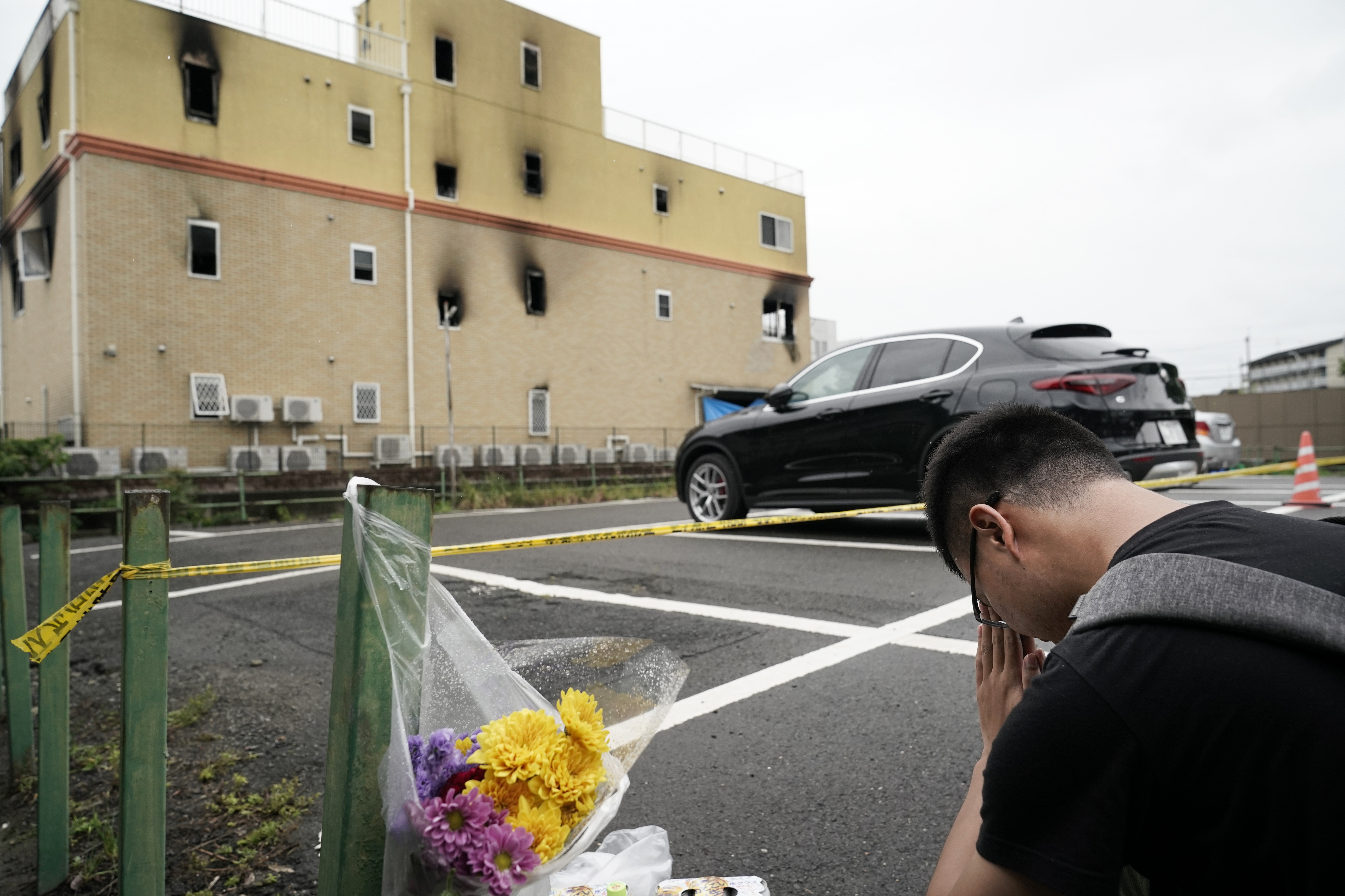 A man prays for victims after placing flowers outside the Kyoto Animation Studio building consumed in an arson attack in Kyoto, Japan on July 19, 2019.