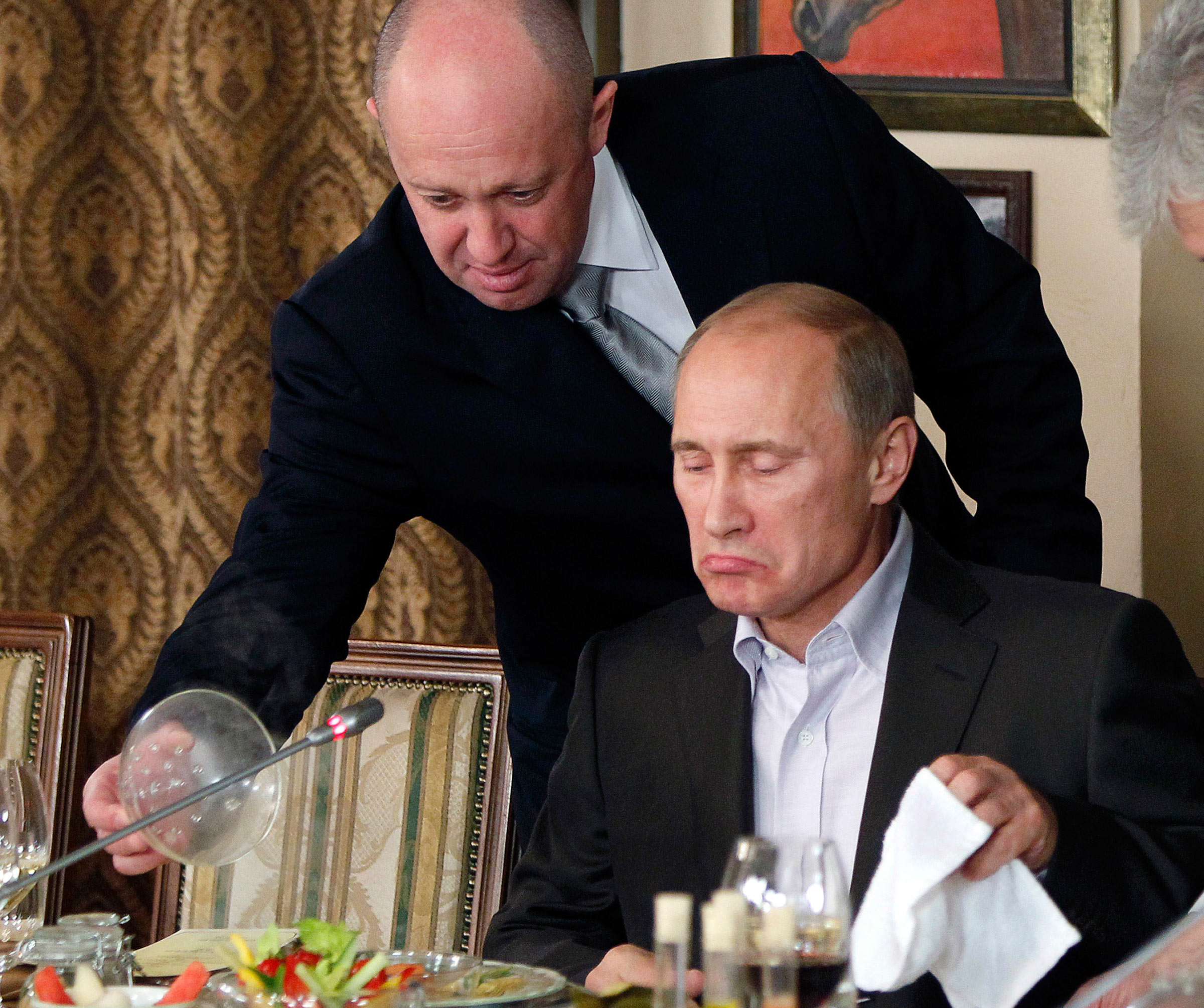 In this Nov. 11, 2011, file photo, Yevgeny Prigozhin, left, serves food to then-Russian Prime Minister Vladimir Putin at Prigozhin's restaurant outside Moscow, Russia.