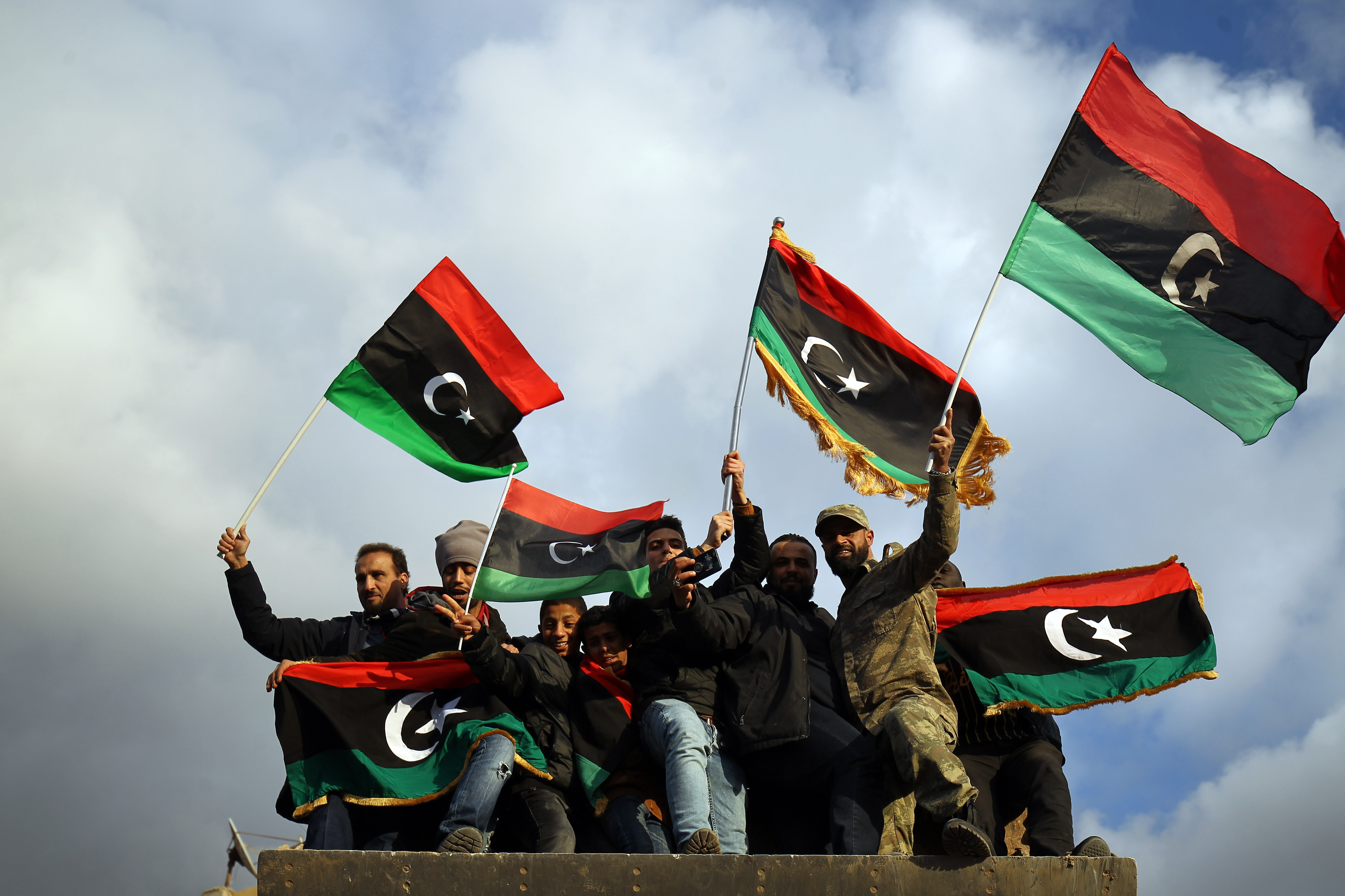 Libyans wave the national flag as they gather to mark the eighth anniversary of the uprising in Libya's second city of Benghazi, on February 17, 2019.