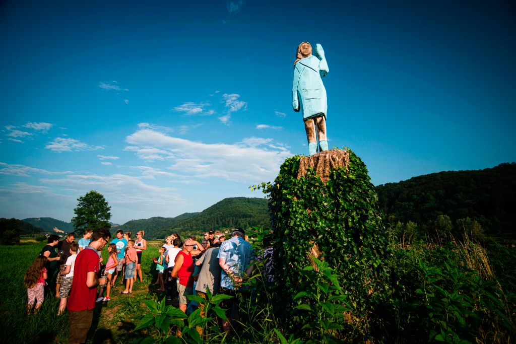 People gather around what conceptual artist Ales 'Maxi' Zupevc claims is the first ever monument of Melania Trump, set in the fields near the town of Sevnica, US First Lady's hometown, during a small inauguration celebration on July 5, 2019.