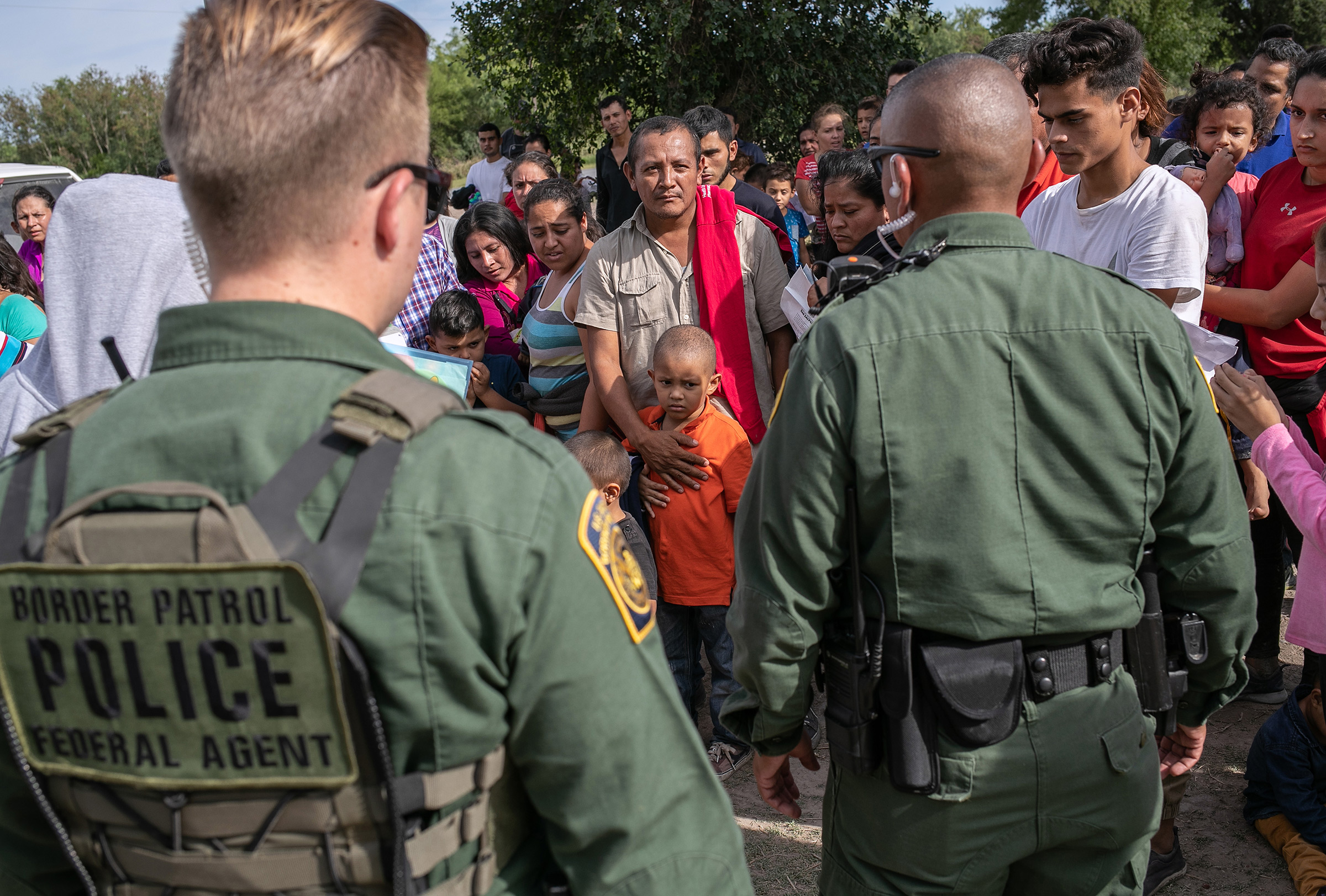 U.S. Border Patrol agents watch over immigrants after taking them into custody on July 02, 2019 in Los Ebanos, Texas.