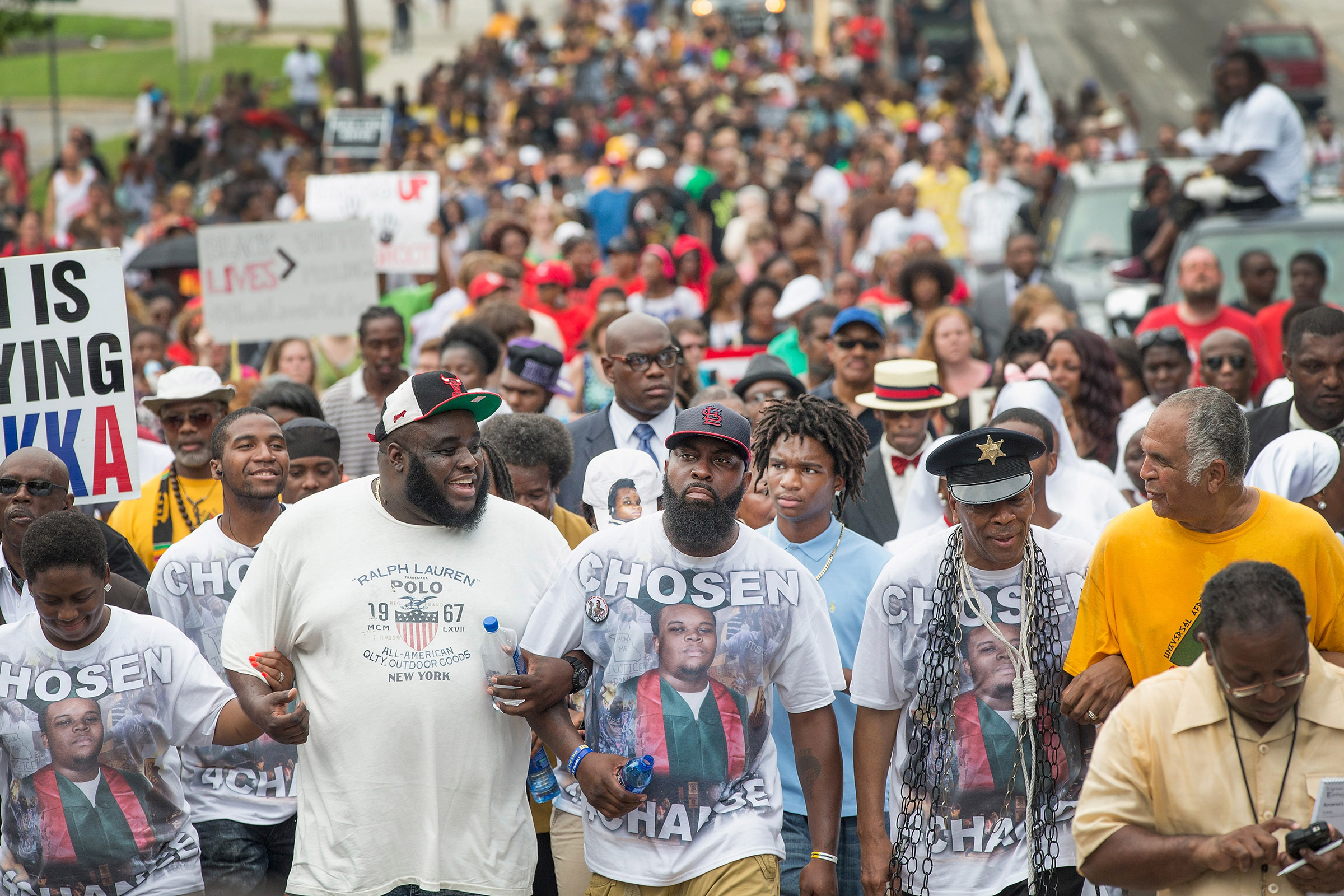 Michael Brown Sr. (center) leads a march from the location where his son Michael Brown Jr. was shot and killed following a memorial service marking the anniversary of his death in Ferguson, Mo. on Aug. 9, 2015.