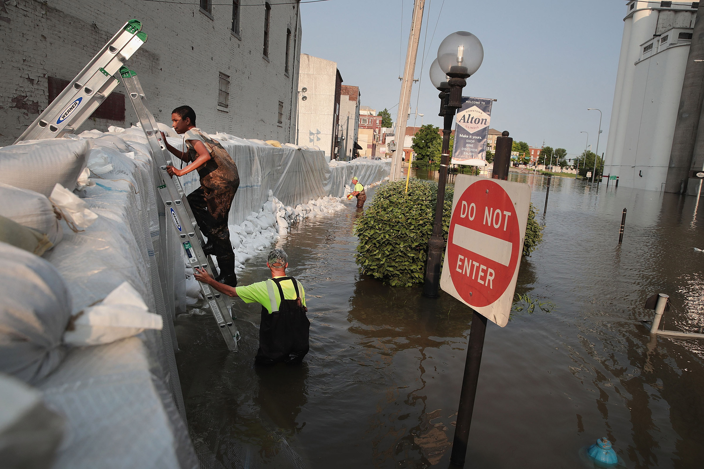 Workers construct a temporary floodwall along Highway 100 to keep floodwater from the Mississippi River out of the historic downtown area in Alton, Ill., on May 31, 2019.