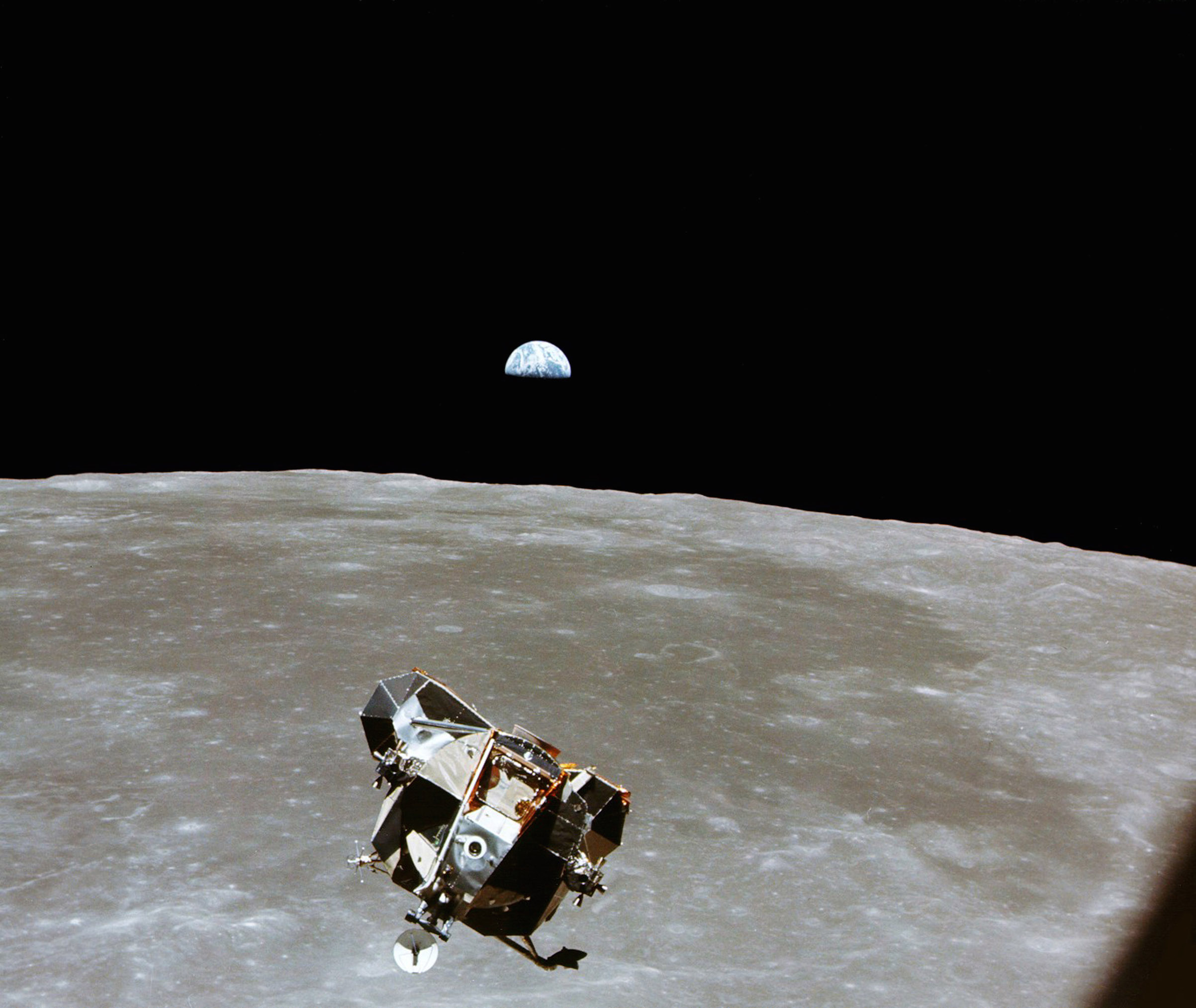 With a half-Earth in the background, the Lunar Module ascent stage with Astronauts Neil Armstrong and Edwin Aldrin Jr. approaches for a rendezvous with the Apollo Command Module manned by Michael Collins, during the Apollo 11 mission in 1969.