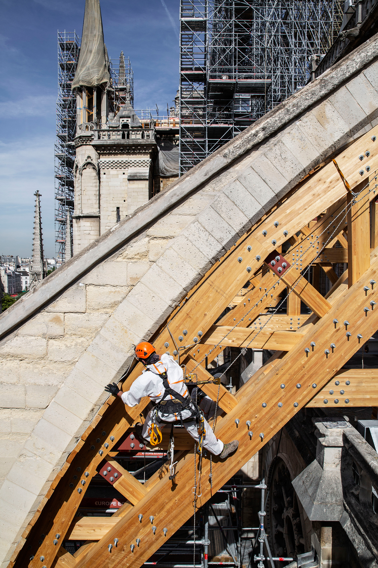 A rope-access technician installs a wooden arch to support a flying buttress on July 22.