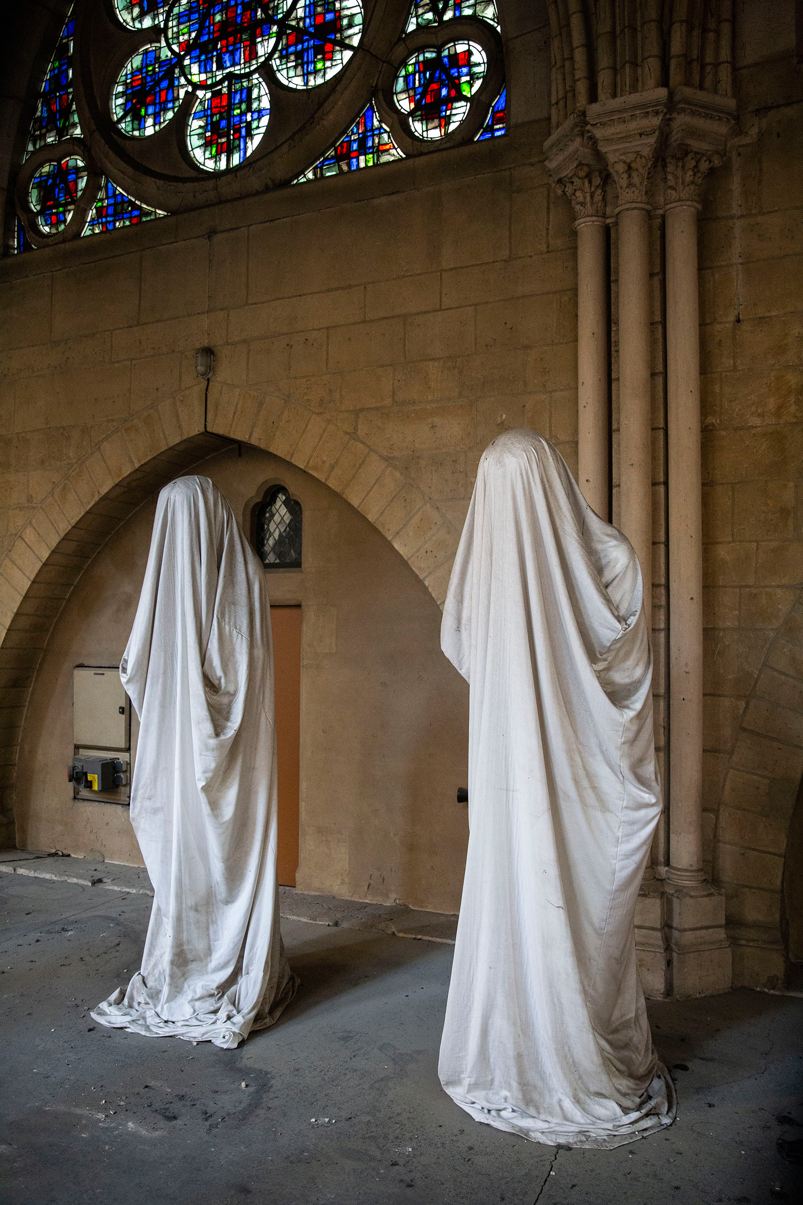 Two statues covered in cloth rest inside the cathedral.