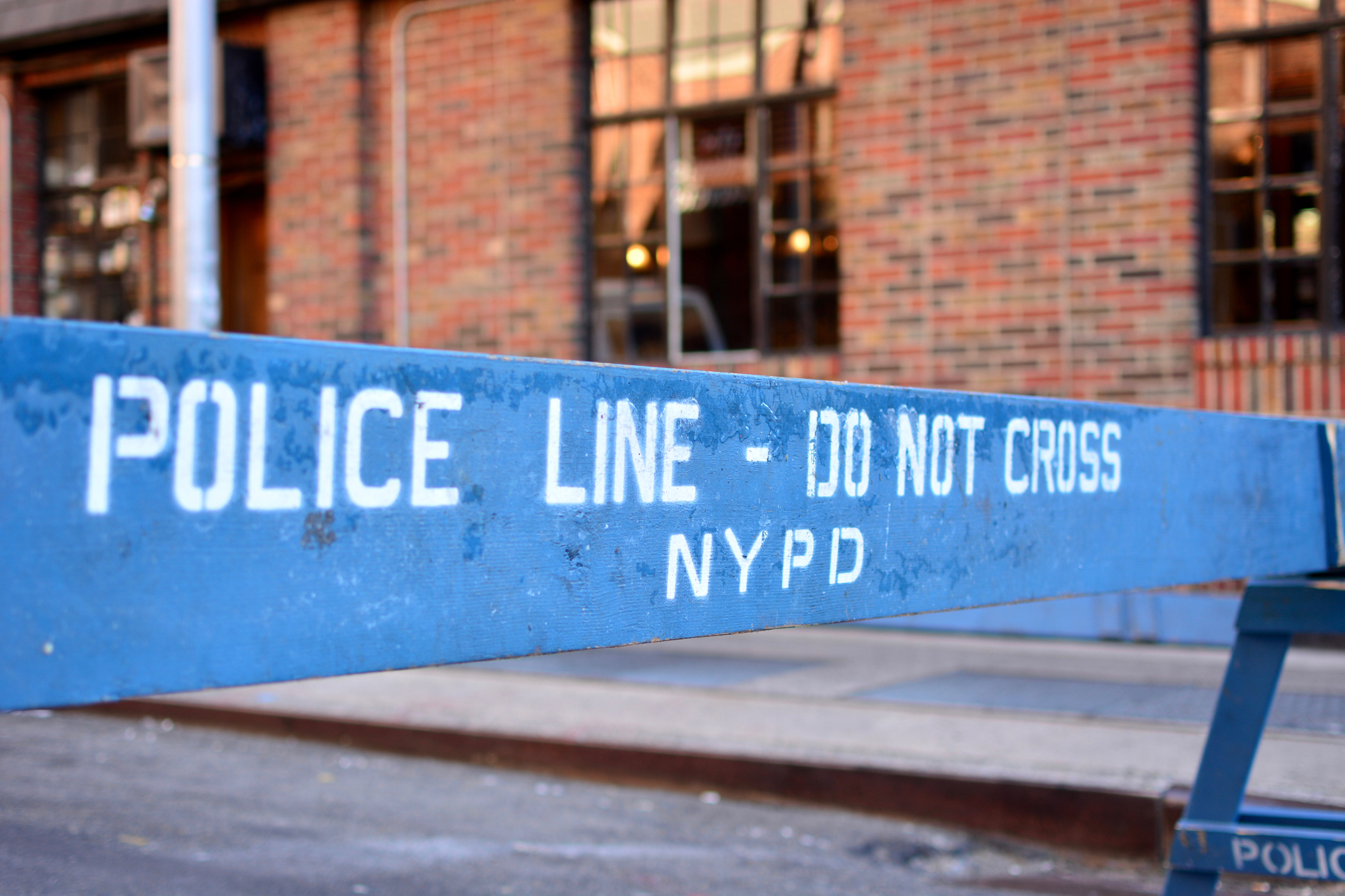 Police line, do not cross sign against a brick wall with windows in New York