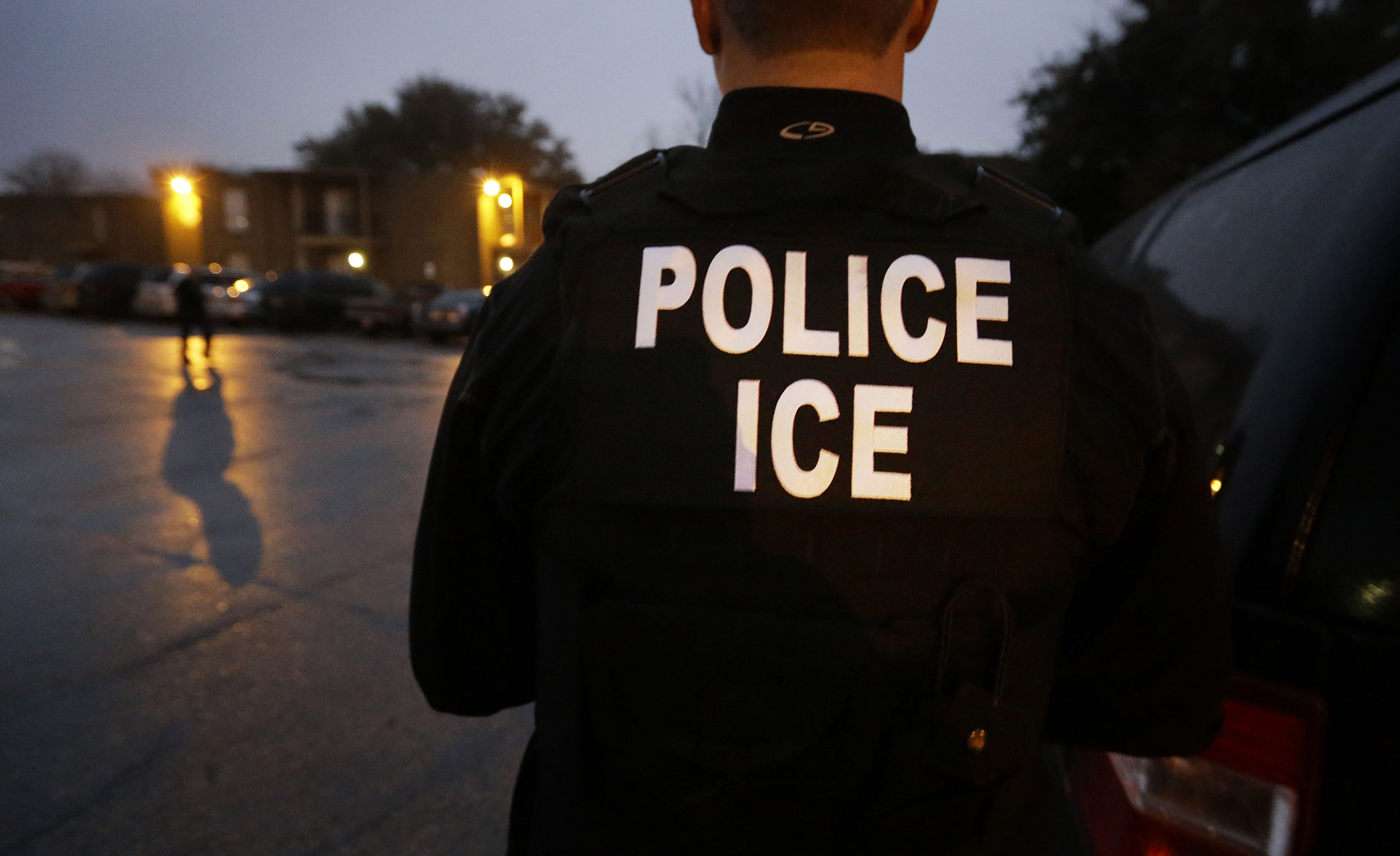 In this March 6, 2015, file photo, U.S. Immigration and Customs Enforcement agents enter an apartment complex looking for a specific undocumented immigrant convicted of a felony during an early morning operation in Dallas. The federal government provided Tuesday, Dec. 5, 2017, the most complete statistical snapshot of immigration enforcement under President Donald Trump, showing Border Patrol arrests plunged to a 45-year low while arrests by deportation officers soared.