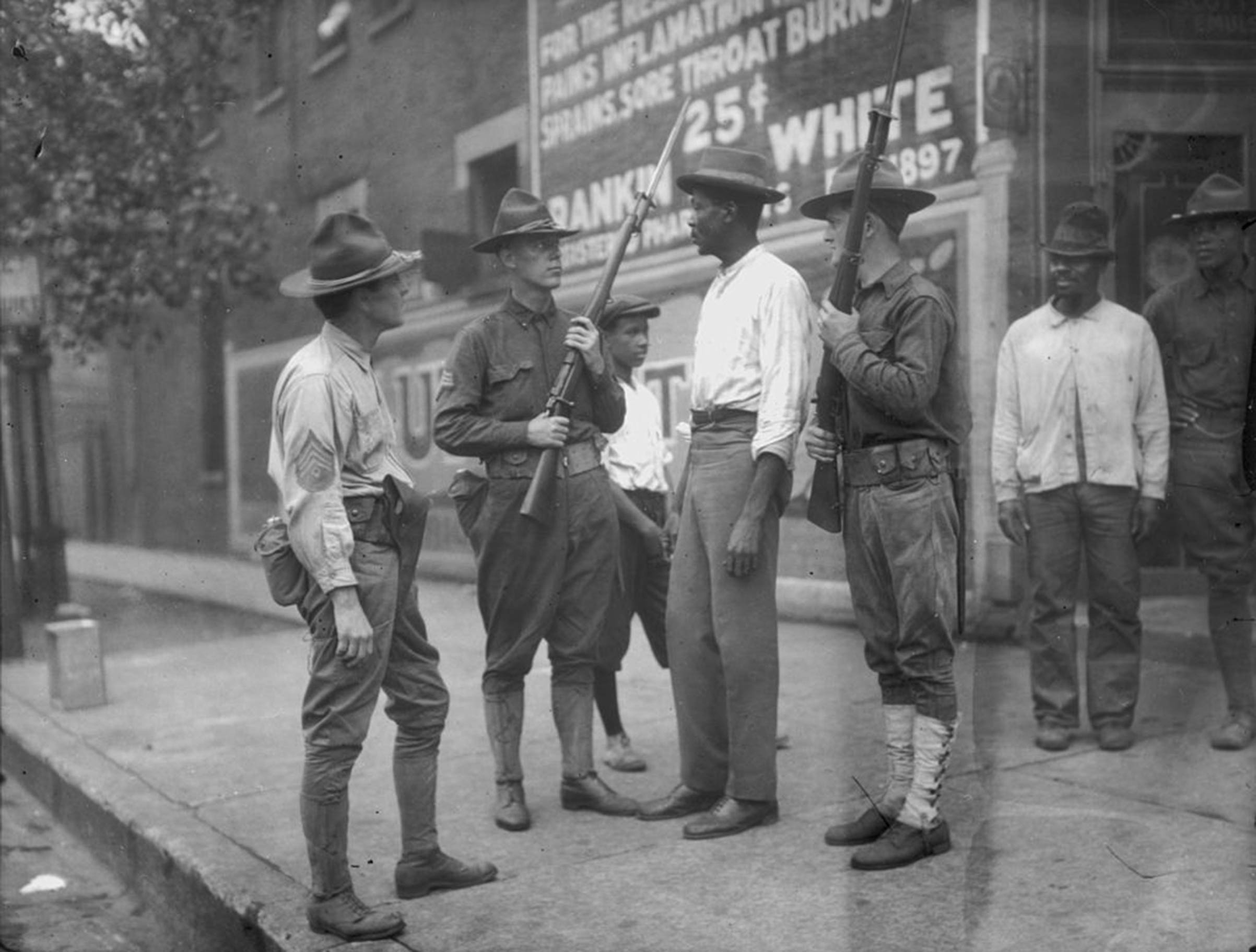 National Guardsmen question an African-American man in Chicago, after Mayor 'Big Bill' Thompson called in the National Guard on July 30, 1919, after three days of rioting.