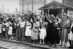 Relatives and friends wave goodbye to a train carrying 1,500