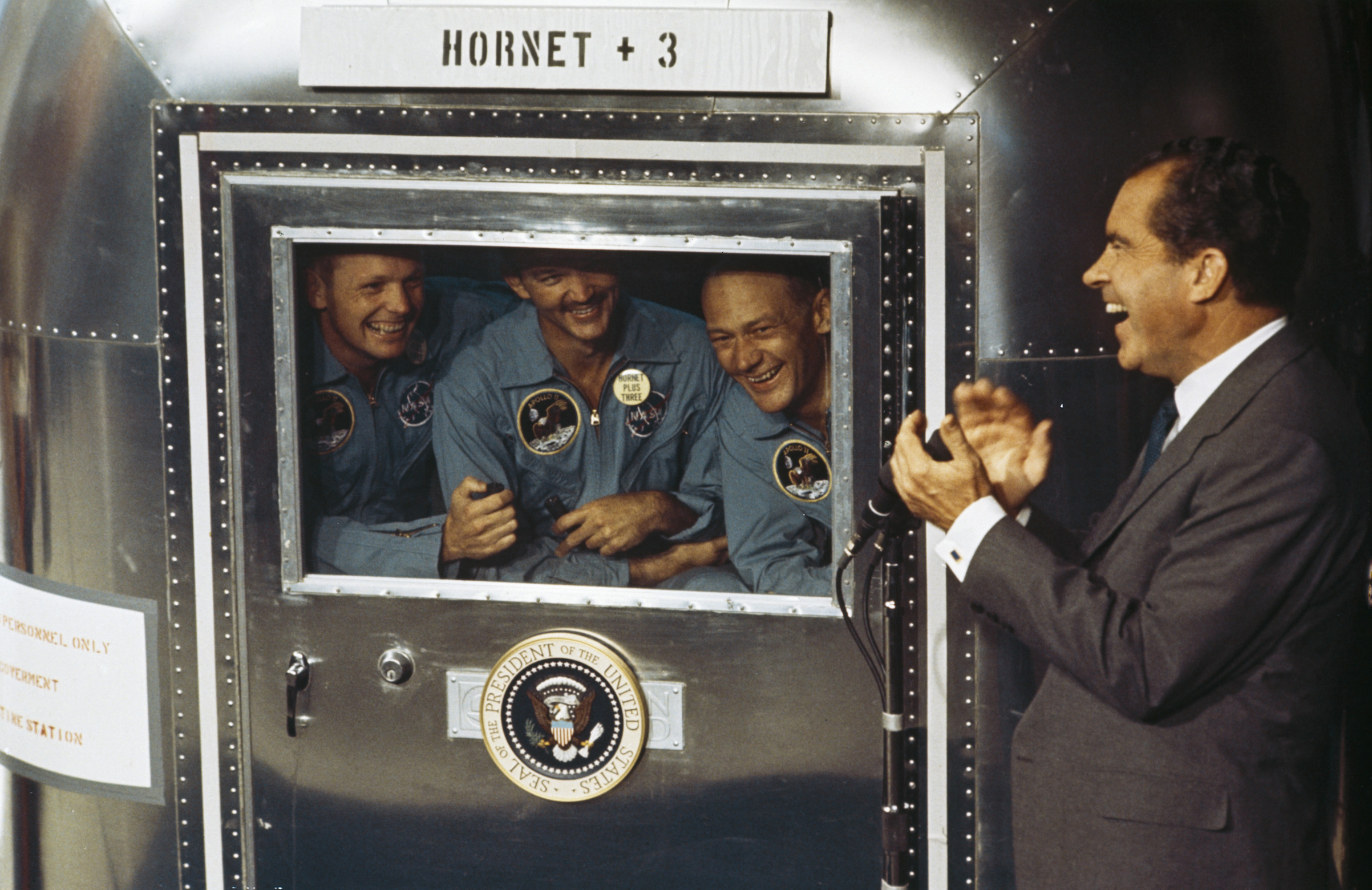 From left to right, Neil Armstrong, Michael Collins and Buzz Aldrin, the crew of the historic Apollo 11 moon landing mission, are subjected to a period of quarantine upon their return to earth. Through the window of their Mobile Quarantine Facility, they hold a conversation with President Richard Nixon.