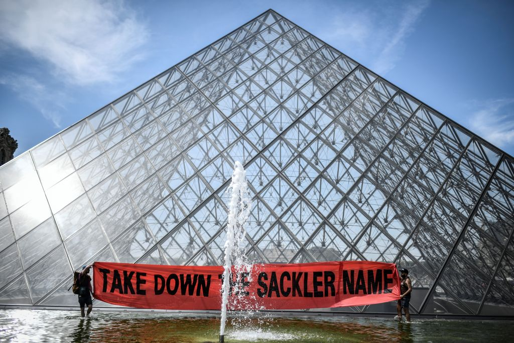 Activists hold a banner reading  Take down the Sackler name  in front of the Pyramid of the Louvre museum in Paris on July 1, 2019.