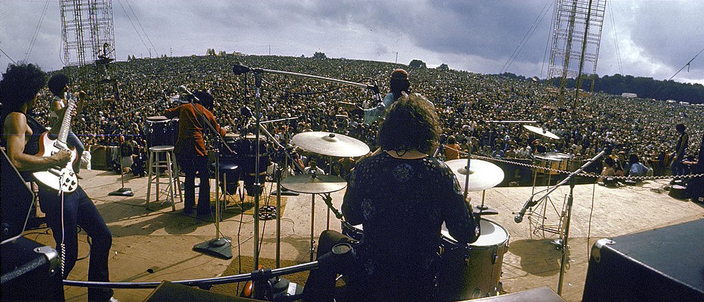 Mexican guitarist Carlos Santana (left) and his band perform on stage to a huge audience at the Woodstock Music & Art Festival, Bethel, New York, August 16, 1969.