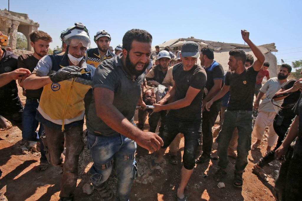 Syrians and members of the Syrian civil defense carry an injured man who was pulled from the rubble of a collapsed building following a reported airstrike in Kafar Roma in the outskirts of Maaret al-Numan in the southern Idlib province on July 25, 2019.