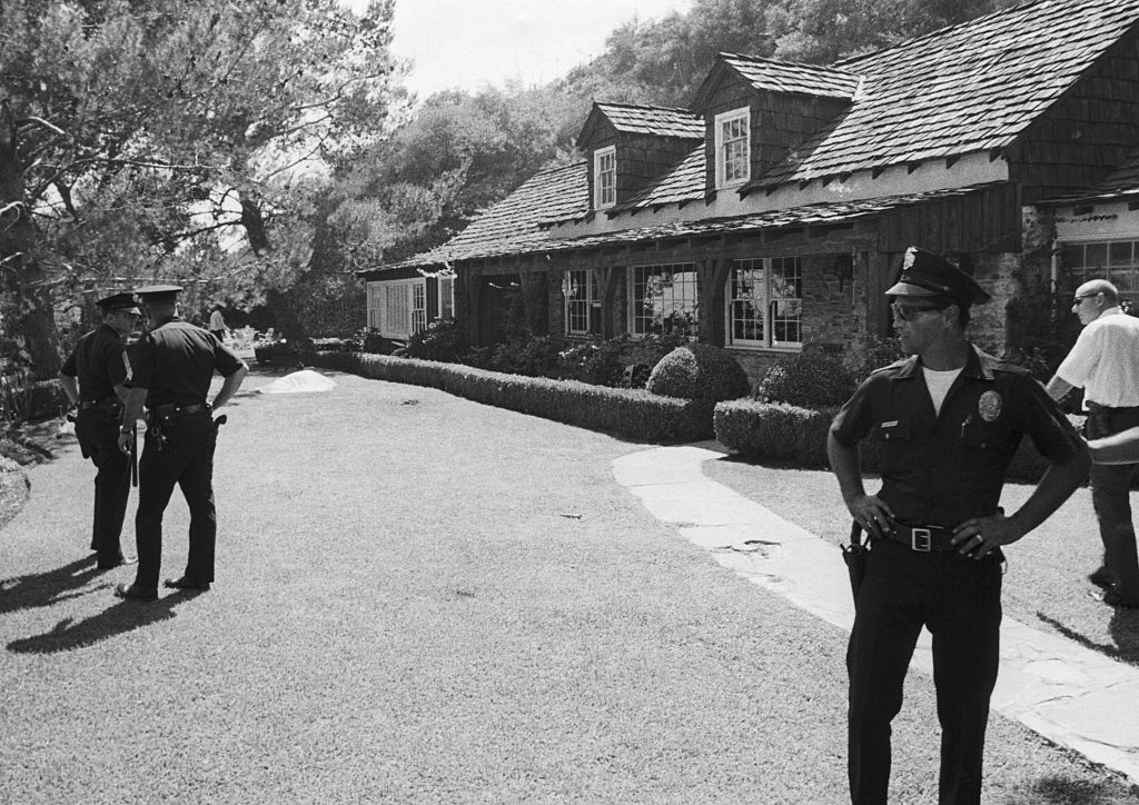 Police guard the rented estate of movie director Roman Polanski after his wife, actress Sharon Tate, and four other persons were found slain August 9th. Visible in the background is a shroud-covered body.