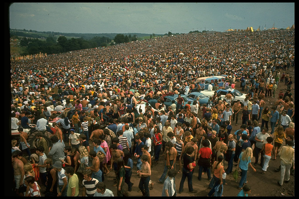 Overall of the huge crowd, looking towards large yellow tents, during the Woodstock Music & Art Fair.