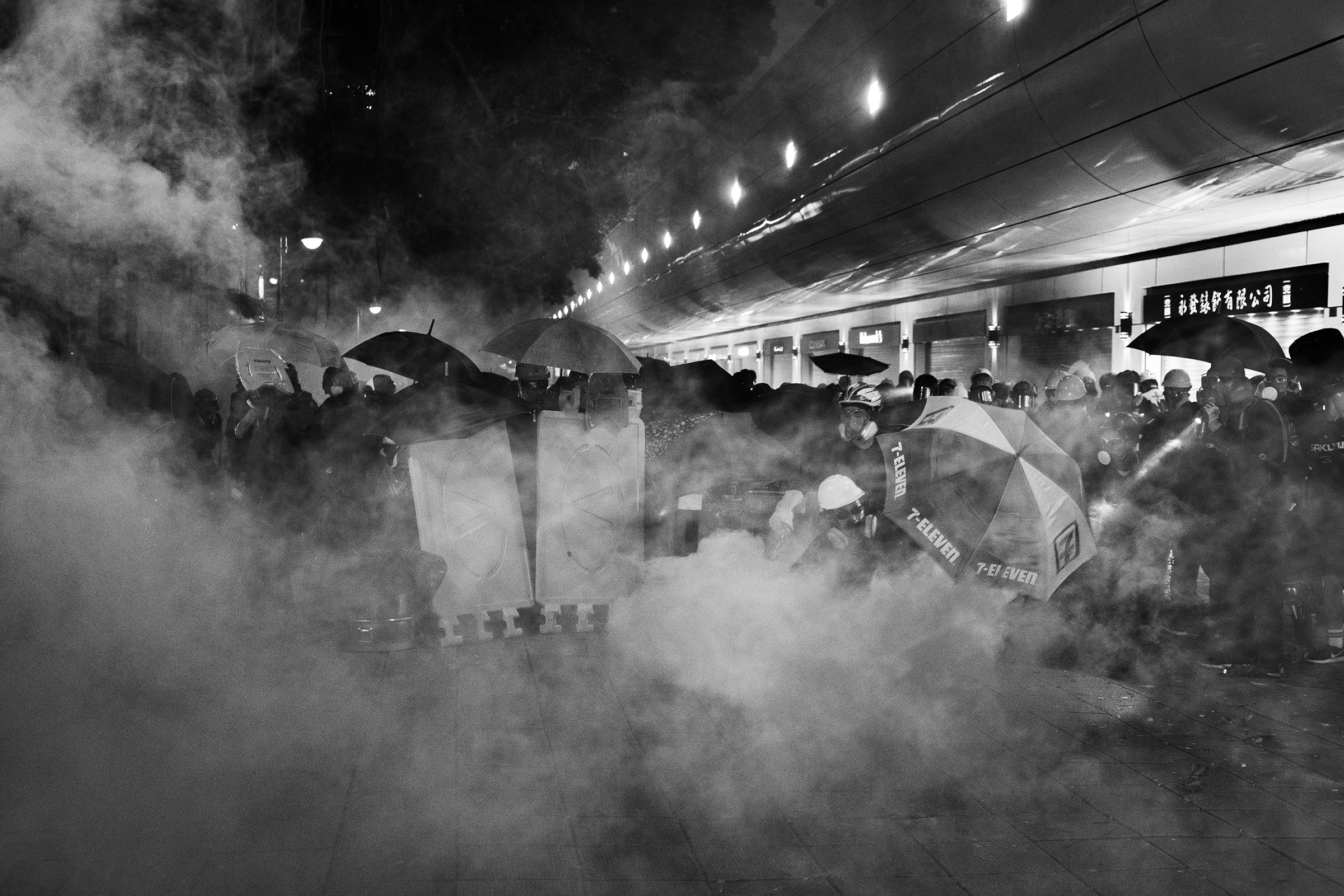 Protesters are tear-gassed by riot police near the Tsim Sha Tsui police station in Kowloon, Hong Kong, on Aug. 11.