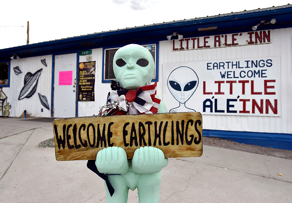 An alien-like statue displays a sign welcoming guests to the Little A'le'Inn restaurant and gift shop in Rachel, Nevada on July 22, 2019.