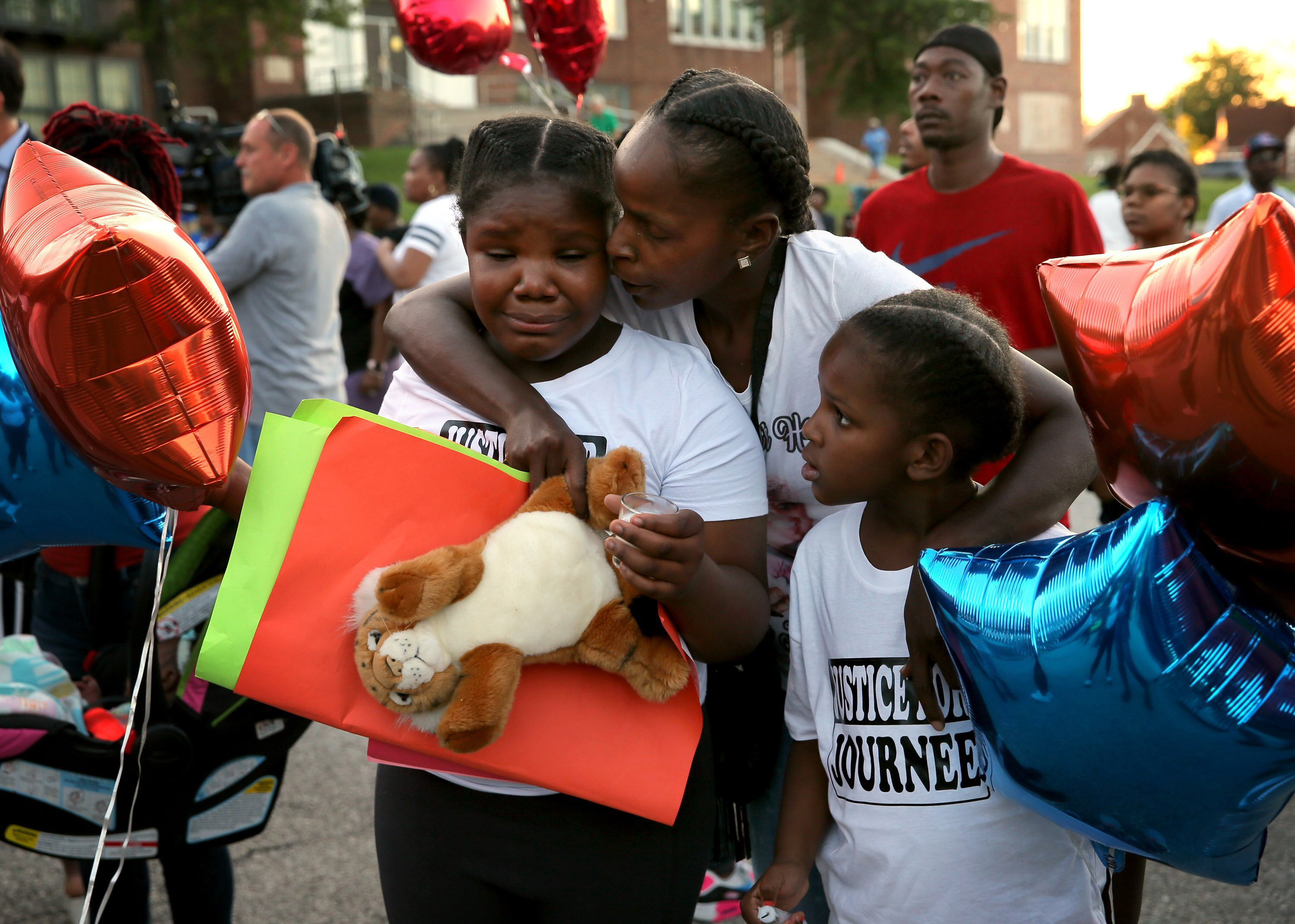 Shardae Edmondson, 11, is consoled by her mother Sharonda Edmondson and sister Zha'lea Thompson, 7, during a vigil for murdered children in St. Louis held at Herzog Elementary School in St. Louis, on Wednesday, Aug. 28, 2019. Shardae and Zha'lea are sisters of 8-year-old Jurnee Thompson who was killed by a stray bullet last Friday night. (David Carson/St. Louis Post-Dispatch via AP)