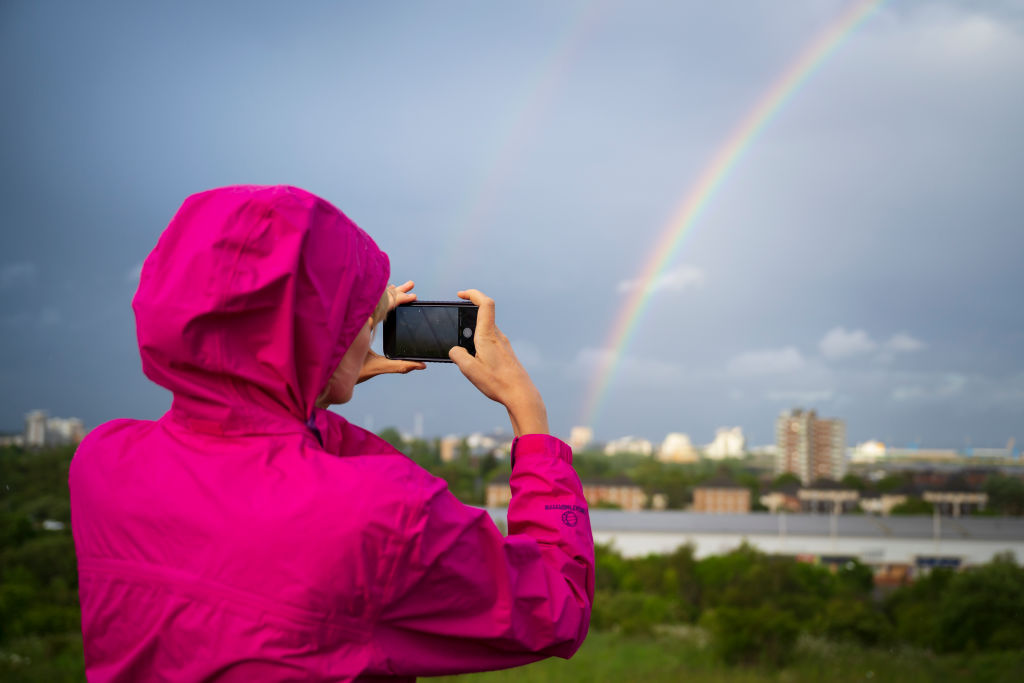 A woman photographs a rainbow over Cardiff City centre on May 27, 2019 in Cardiff, United Kingdom.