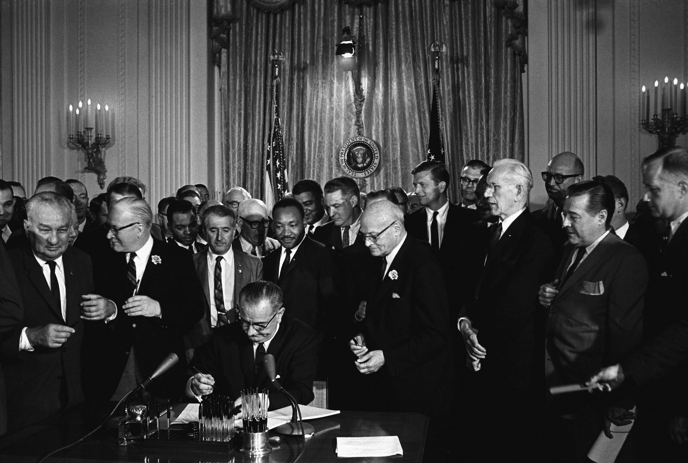 President Lyndon Johnson, seated, signing Civil Rights Act. Behind Johnson is Martin Luther King Jr. 1964.