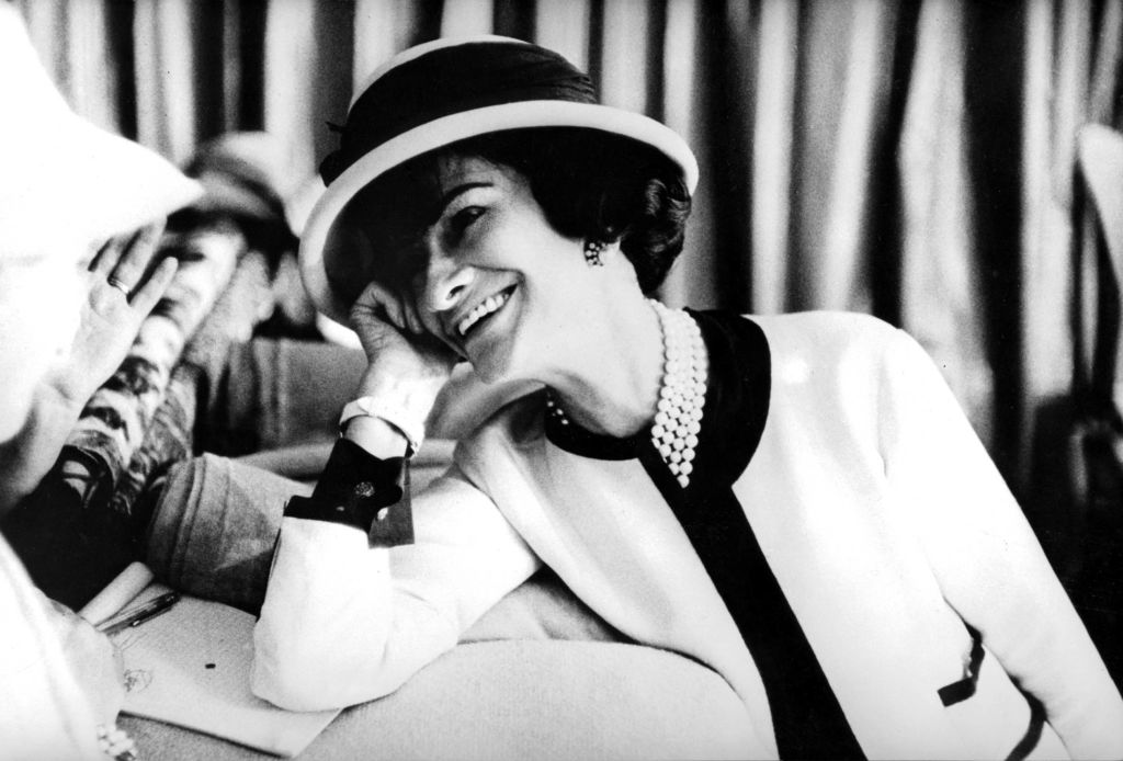 Fashion designer Coco Chanel photographed in the 1950s in one of her famous white suits.