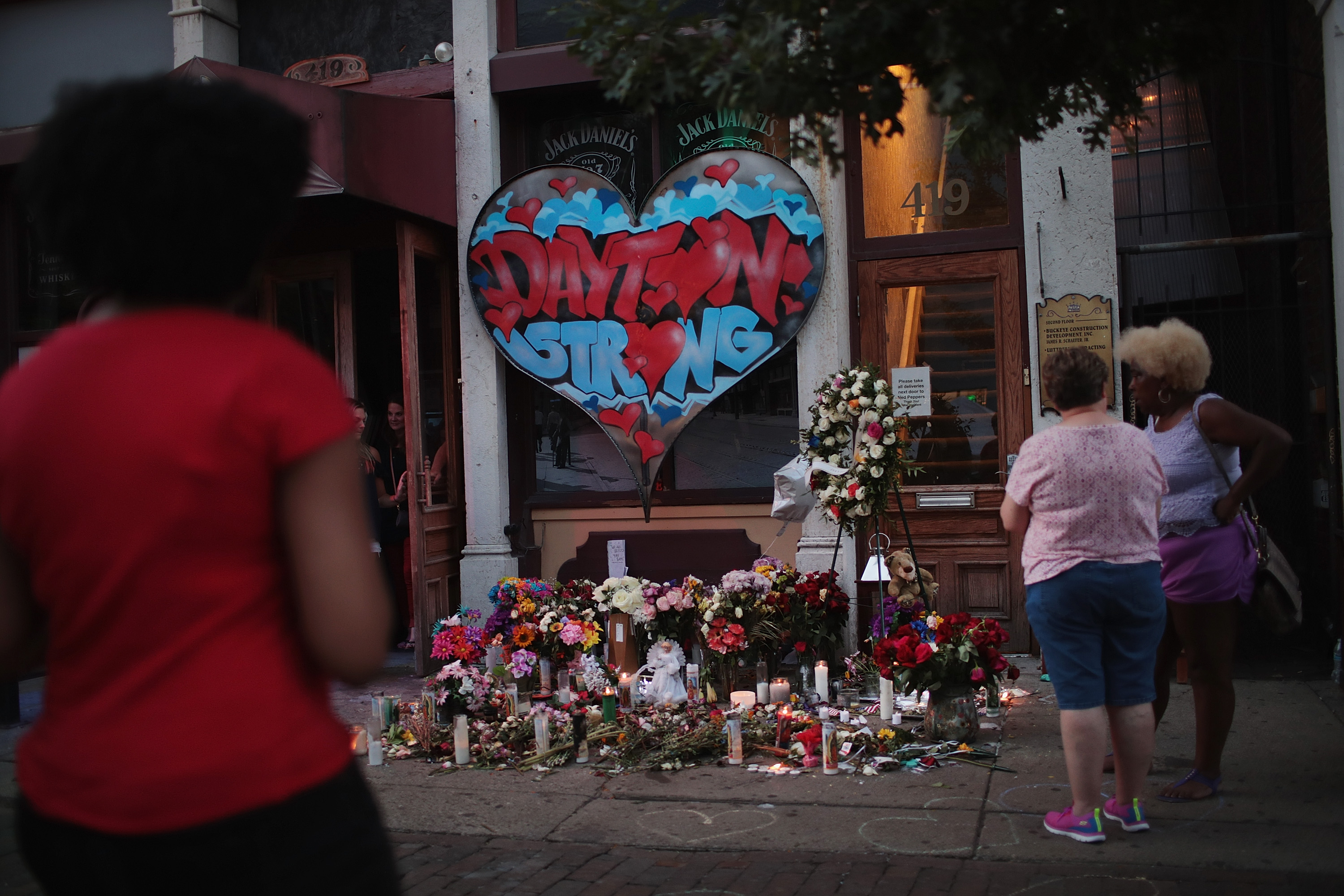 People congregate around a memorial to those killed in a mass shooting on August 06, 2019 in Dayton, Ohio.  Nine people were killed and another 27 injured when a gunman identified as 24-year-old Connor Betts opened fire with a AR-15 style rifle in the popular entertainment district.