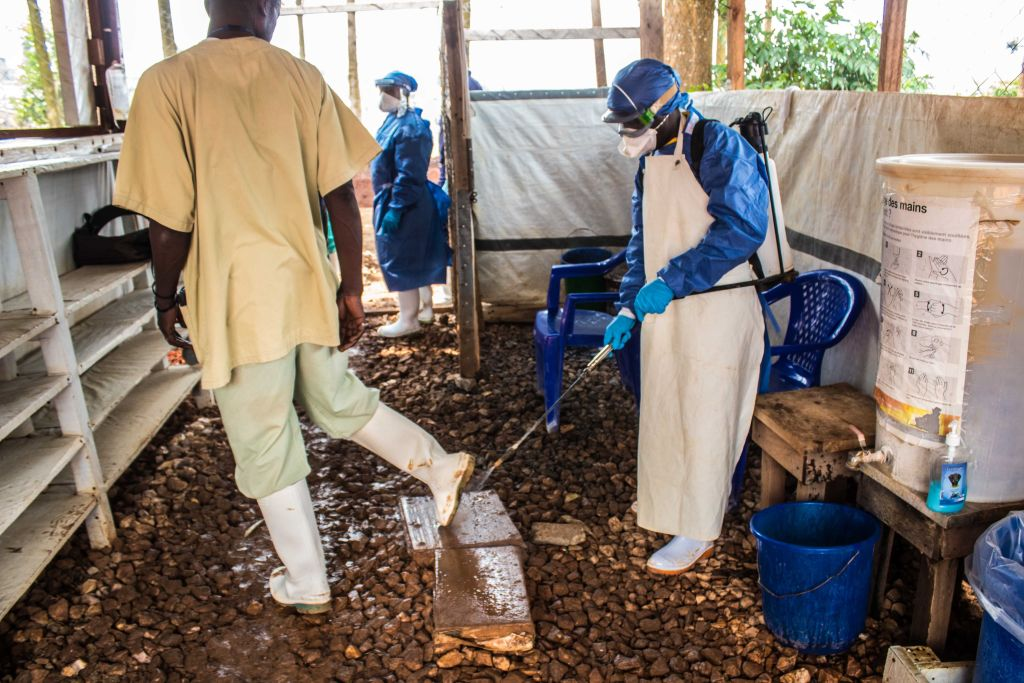 A healthcare worker disinfects a health center with chlorinated water to take precautions against Ebola in Butembo, Democratic Republic of the Congo on July 27, 2019.