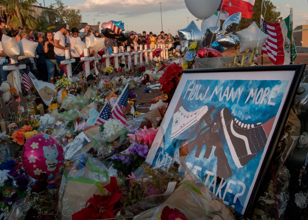 People pray and pay their respects at the makeshift memorial for victims of the shooting that left a total of 22 people dead at the Cielo Vista Mall WalMart (background) in El Paso, Texas, on August 6, 2019.