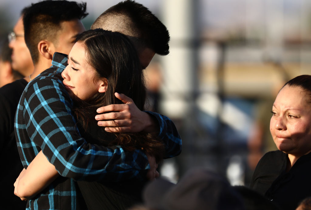 Mourners embrace at a vigil honoring Horizon High School sophomore Javier Amir Rodriguez, who lost his life in a mass shooting in nearby El Paso, on August 5, 2019 in Horizon City, Texas. The vigil was held at the school's football field.