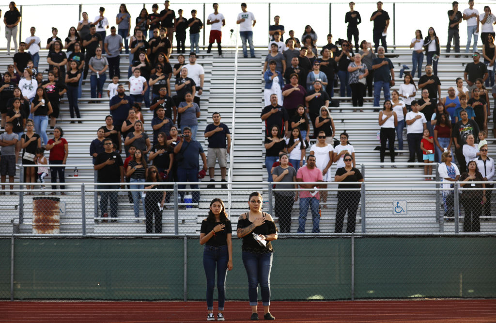 People stand for the national anthem at a vigil honoring Horizon High School sophomore Javier Amir Rodriguez, who lost his life in a mass shooting in nearby El Paso, on August 5, 2019 in Horizon City, Texas. The vigil was held at the school's football field. At least 22 people were killed at the shooting August 3. A 21-year-old male suspect remains in custody in El Paso which sits along the U.S.-Mexico border.