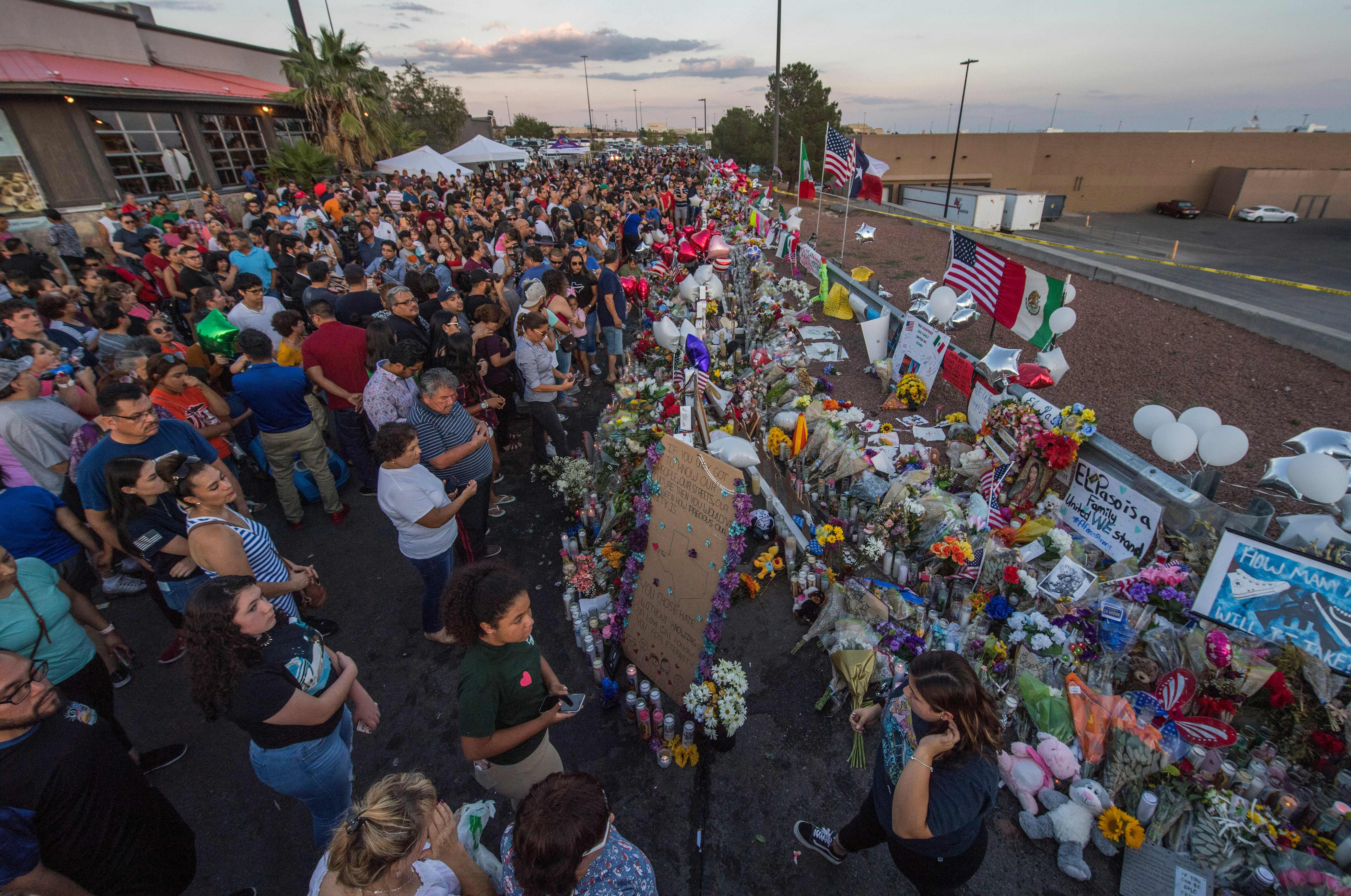 People pray and pay their respects at the makeshift memorial for victims of the shooting that left a total of 22 people dead at the Cielo Vista Mall WalMart (background) in El Paso, Texas, on August 6, 2019. - US President Donald Trump on Monday urged Republicans and Democrats to agree on tighter gun control and suggested legislation could be linked to immigration reform after two shootings left 30 people dead and sparked accusations that his rhetoric was part of the problem.