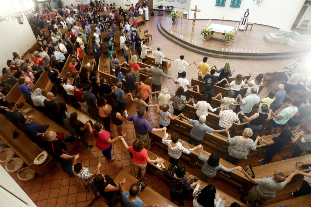 People hold hands during a vigil for victims at St Pius X Church after a mass shooting in El Paso on August 3, 2019, which left at least 20 people dead.
