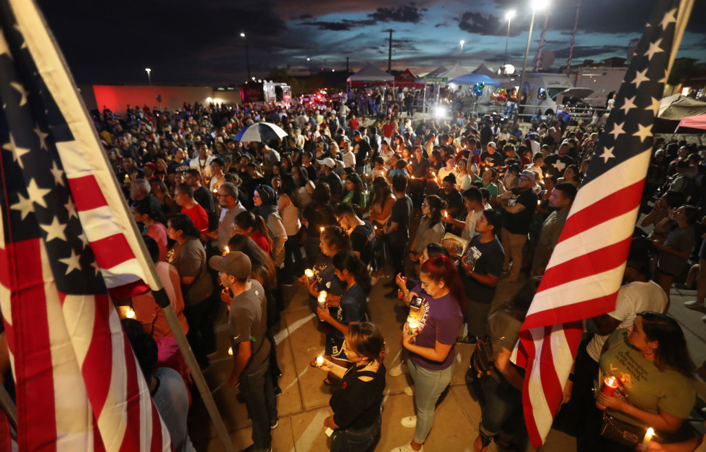 People attend a candlelight vigil at a makeshift memorial honoring victims of a mass shooting which left at least 22 people dead in El Paso, Texas on August 7, 2019.