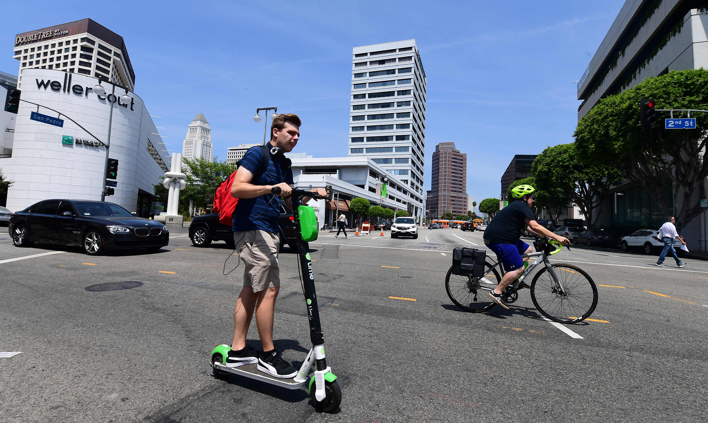 A commuter rides an e-scooter across a Los Angeles street on August 22, 2019, where an e-scooter enforcement task force has been launched in an effort to ensure riders follow the laws.
