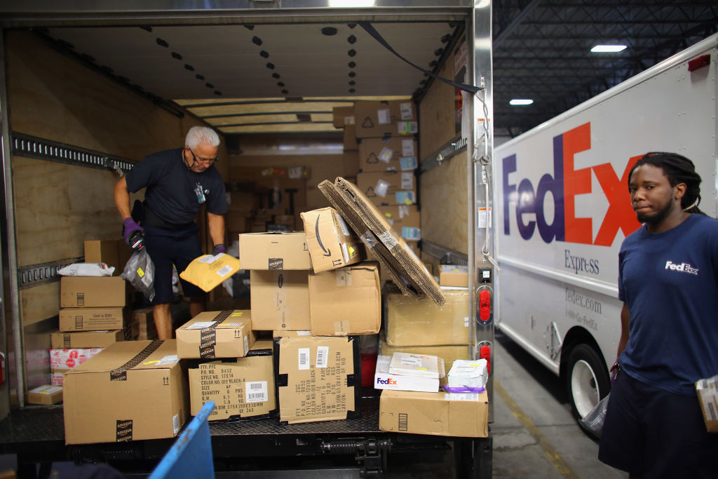 FedEx employees, Victor Alvarez (L) and Ricardo Bruno, sort through items including Amazon shipments being shipped through the Fedex World Service Center on December 10, 2012 in Doral, Florida.