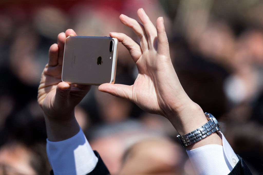 A guest attendee uses an Apple Inc.  iPhone to take a photograph of Japan's Prime Minister Shinzo Abe (not pictured) during the cherry blossom viewing party at the Shinjuku Gyoen National Garden on April 13, 2019 in Tokyo, Japan.
