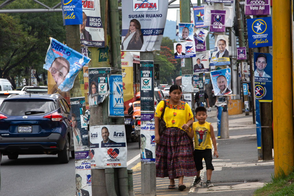 Pedestrians walk past campaign signs displayed during presidential elections in Guatemala City, Guatemala, on Sunday, June 16, 2019.