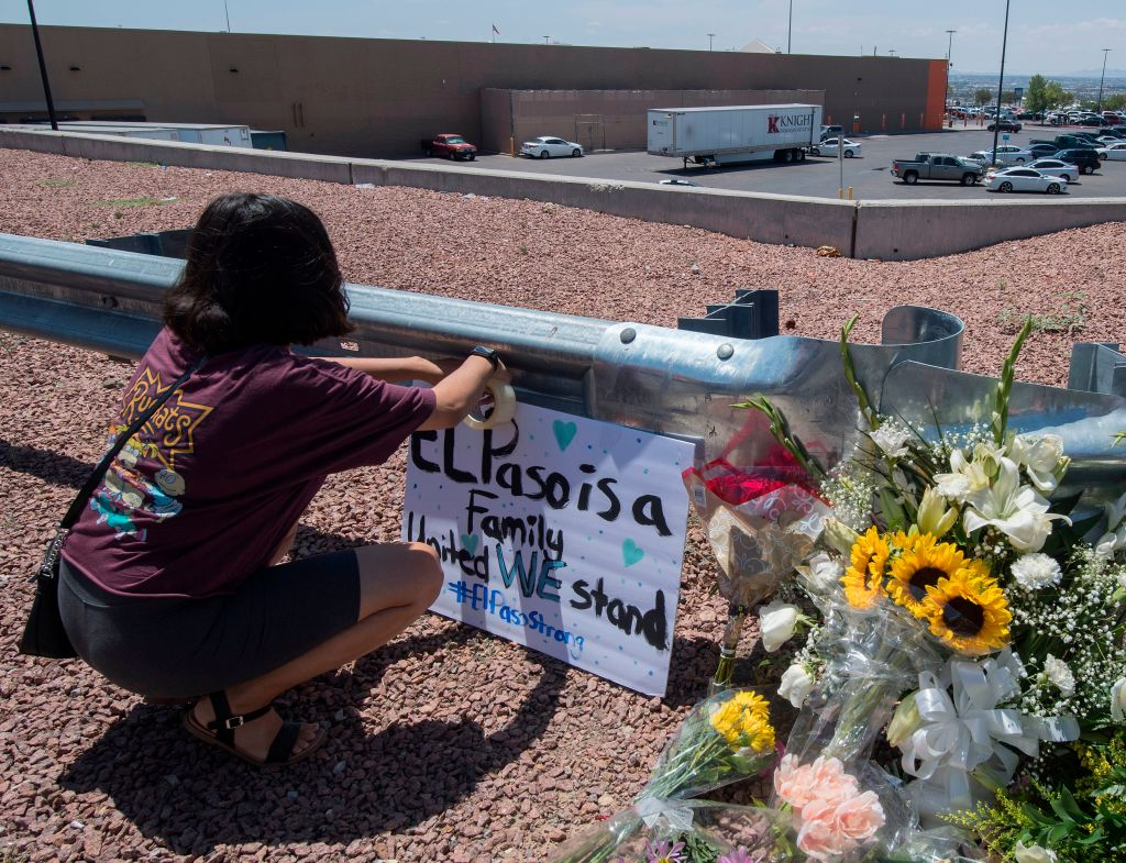 A woman places a Stay Strong sign beside a makeshift memorial outside the Cielo Vista Mall Wal-Mart (background) where a shooting left 20 people dead in El Paso, Texas, on August 4, 2019.