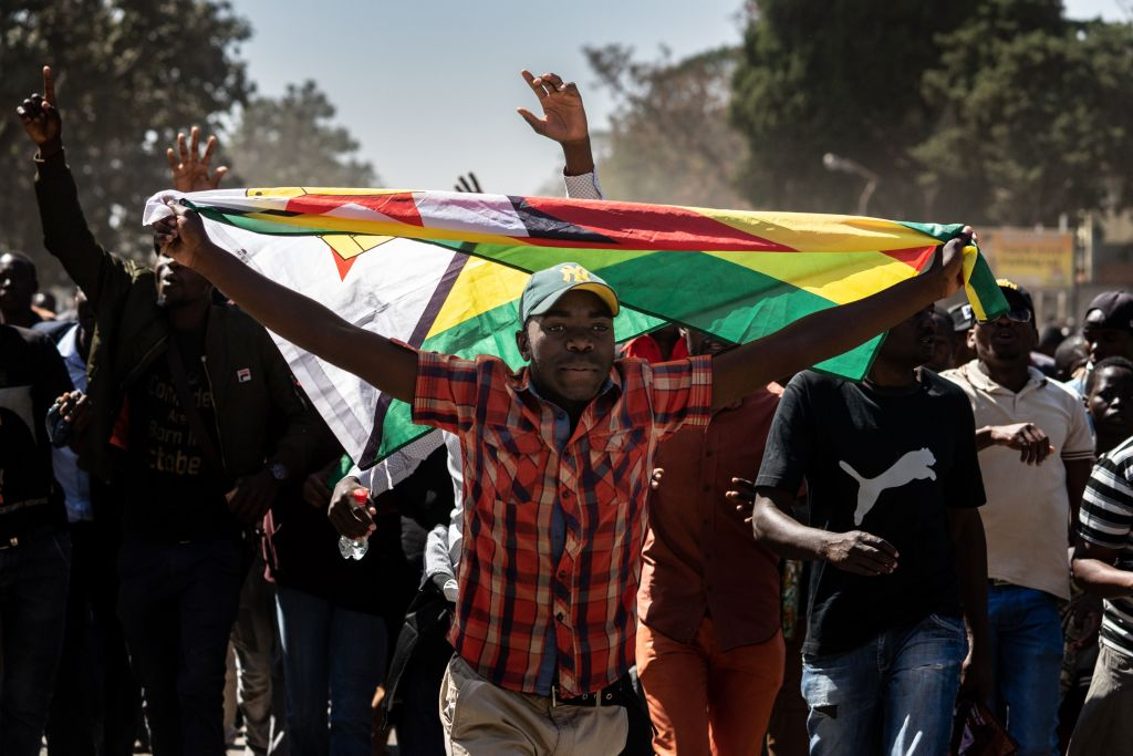 A man holding Zimbabwe's national flag walks with other protesters as they march in the streets of Harare on August 16, 2019. Riot police in Zimbabwe fired teargas and beat demonstrators on August 16 during a crackdown on opposition supporters who have taken to Harare's streets despite a protest ban.