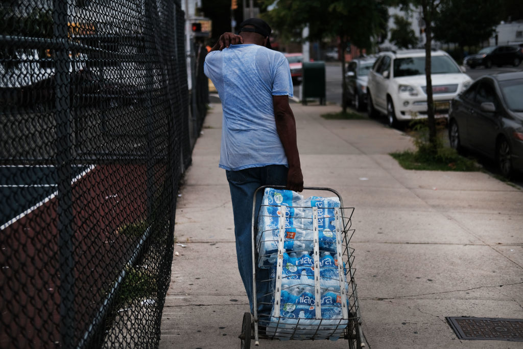 People wait in line for bottled water at a recreation center on August 13, 2019 in Newark, New Jersey. Residents of Newark, the largest city in New Jersey, are to receive free water after lead was found in the tap water.